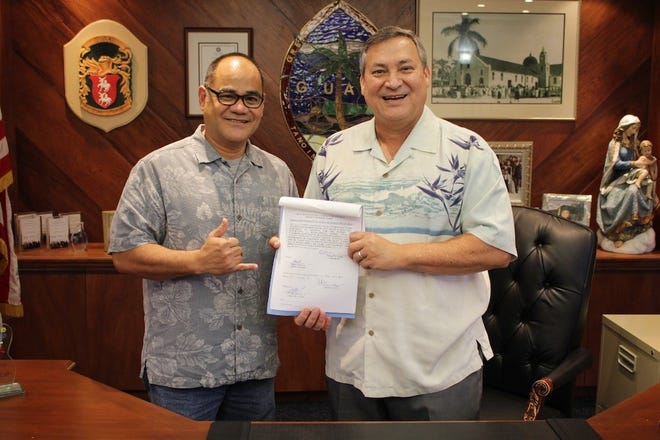Gov. Eddie Calvo stands with Wolverines Soccer Club president Joe Roberto after the governor signed into law on Dec. 28, 2018 Sen. Frank Aguon Jr.'s Bill 364, which seeks to allow a property near Talofofo Elementary School to be used to promote youth soccer and athleticism.