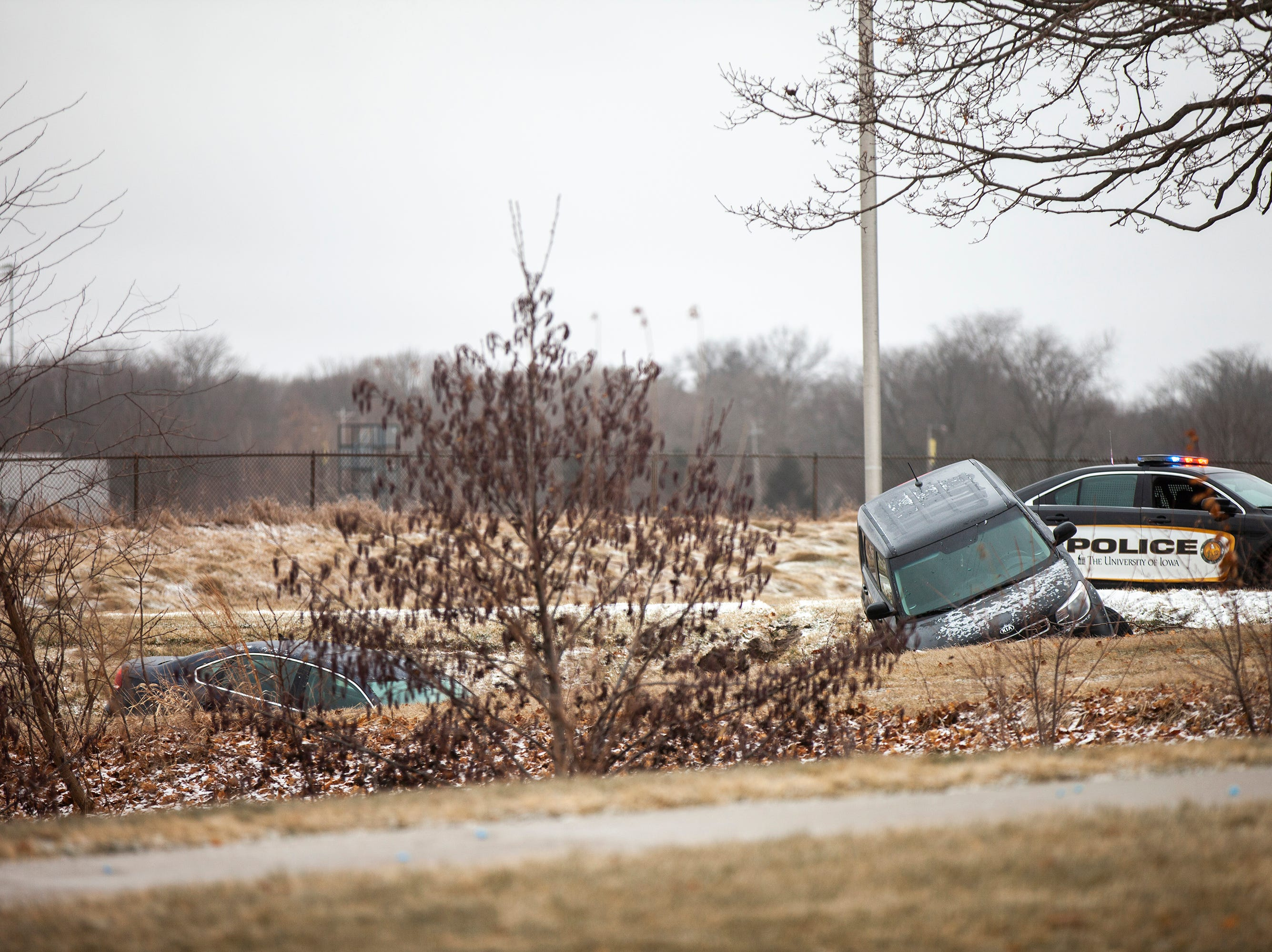A University of Iowa police officer responds to an incident where two vehicles drove off the road due to icy conditions on Friday, Dec. 28, 2018, off of Mormon Trek Blvd near Hawkeye Court on the west side of Iowa City.