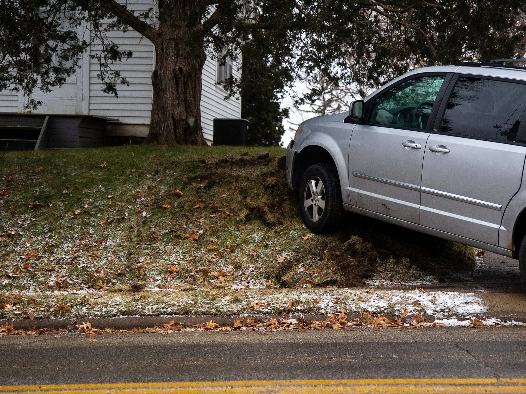 A minivan's front end is stuck on a hill next to a fire hydrant during icy road conditions on Friday, Dec. 28, 2018, off of Court Street near 2nd Avenue on the east side of Iowa City.