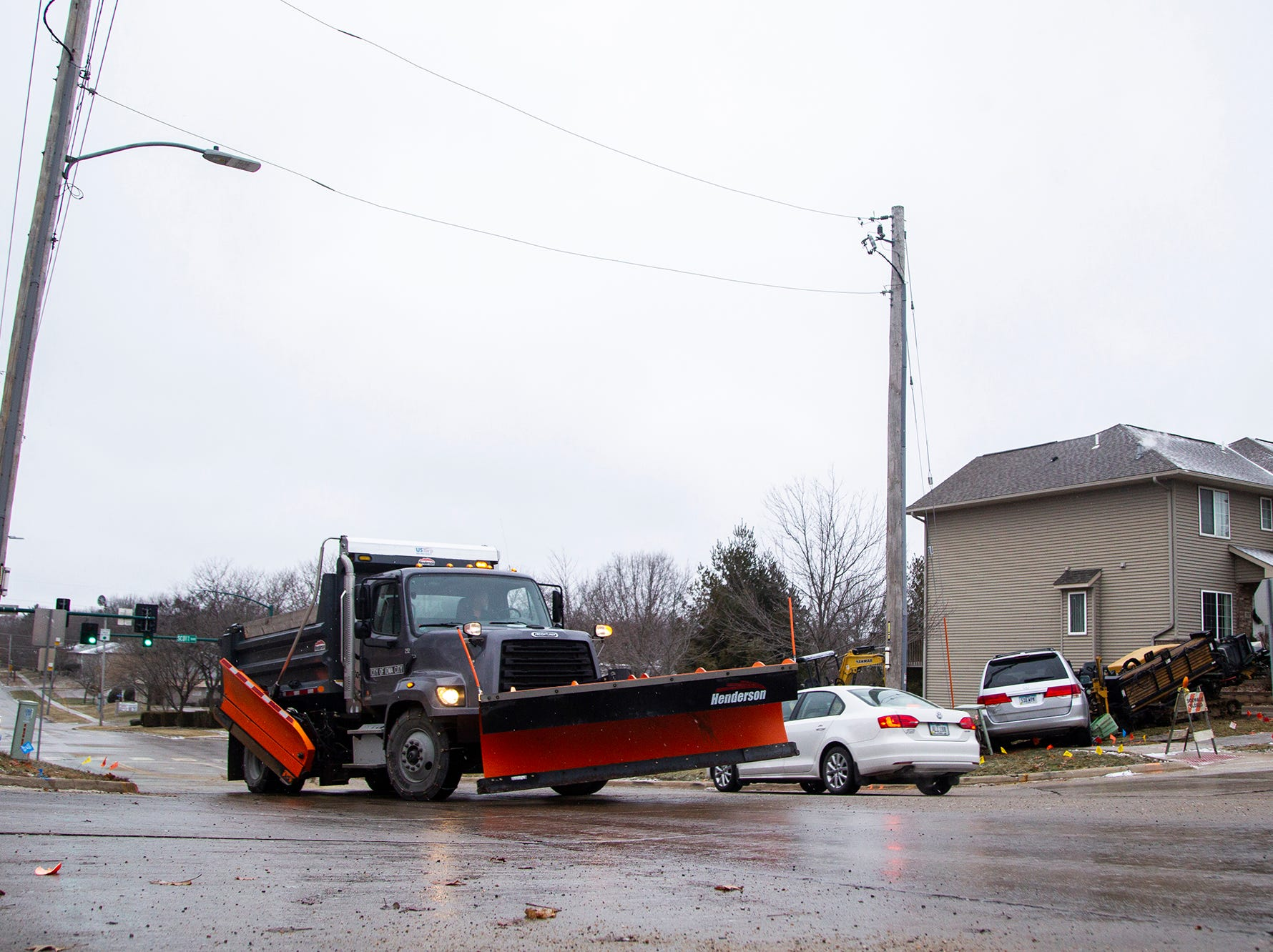An Iowa City snowplow drives past a scene where a minivan hit an electrical box during icy road conditions on Friday, Dec. 28, 2018, off of Court Street near Scott Park Drive on the east side of Iowa City.