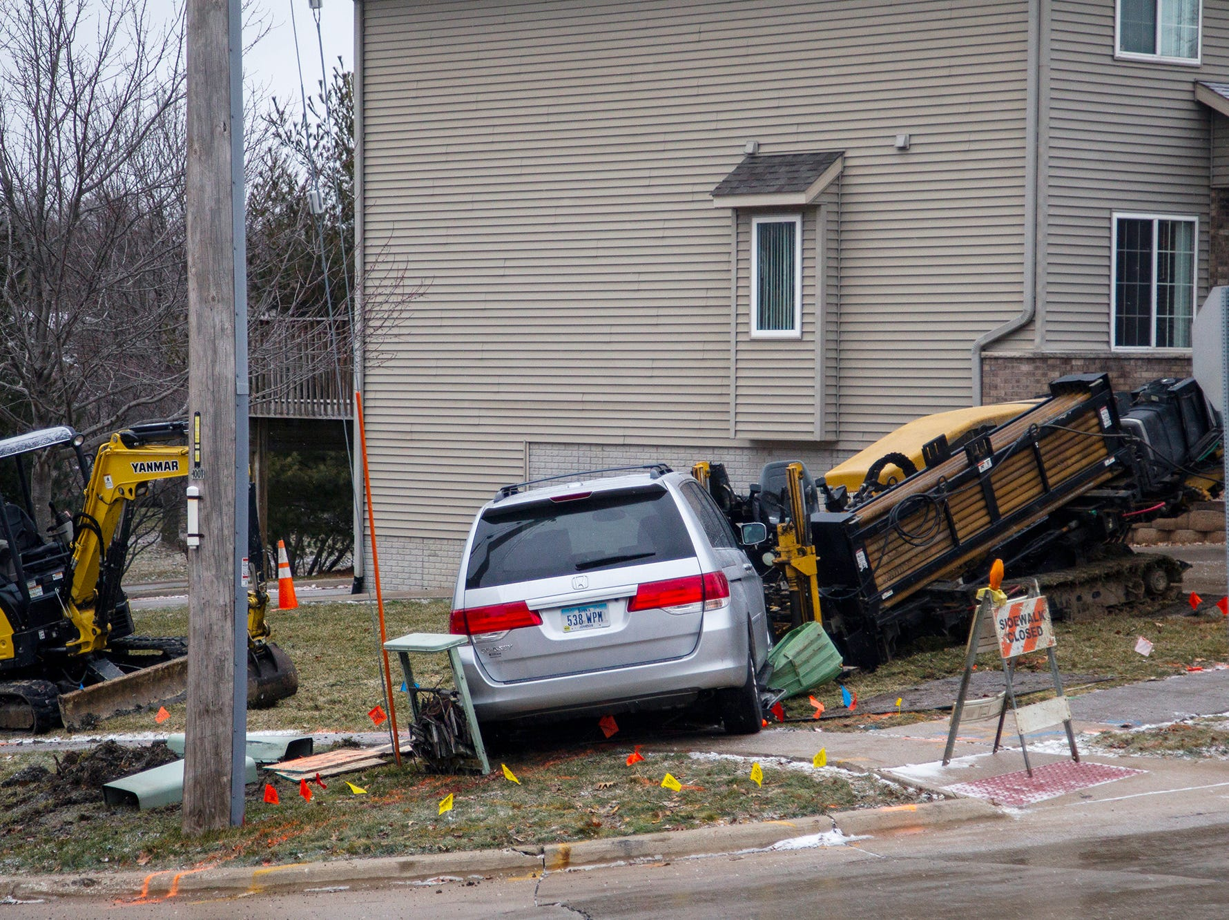 A minivan sits on top of an electrical box it drove over during icy road conditions on Friday, Dec. 28, 2018, off of Court Street near Scott Park Drive on the east side of Iowa City.