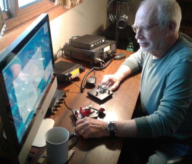 Ham radio operator Dennis Boyd enjoys his contact by voice and Morse Code with other amateur radio hobbyists from around the country, broadcasting from this room in his North Liberty home.