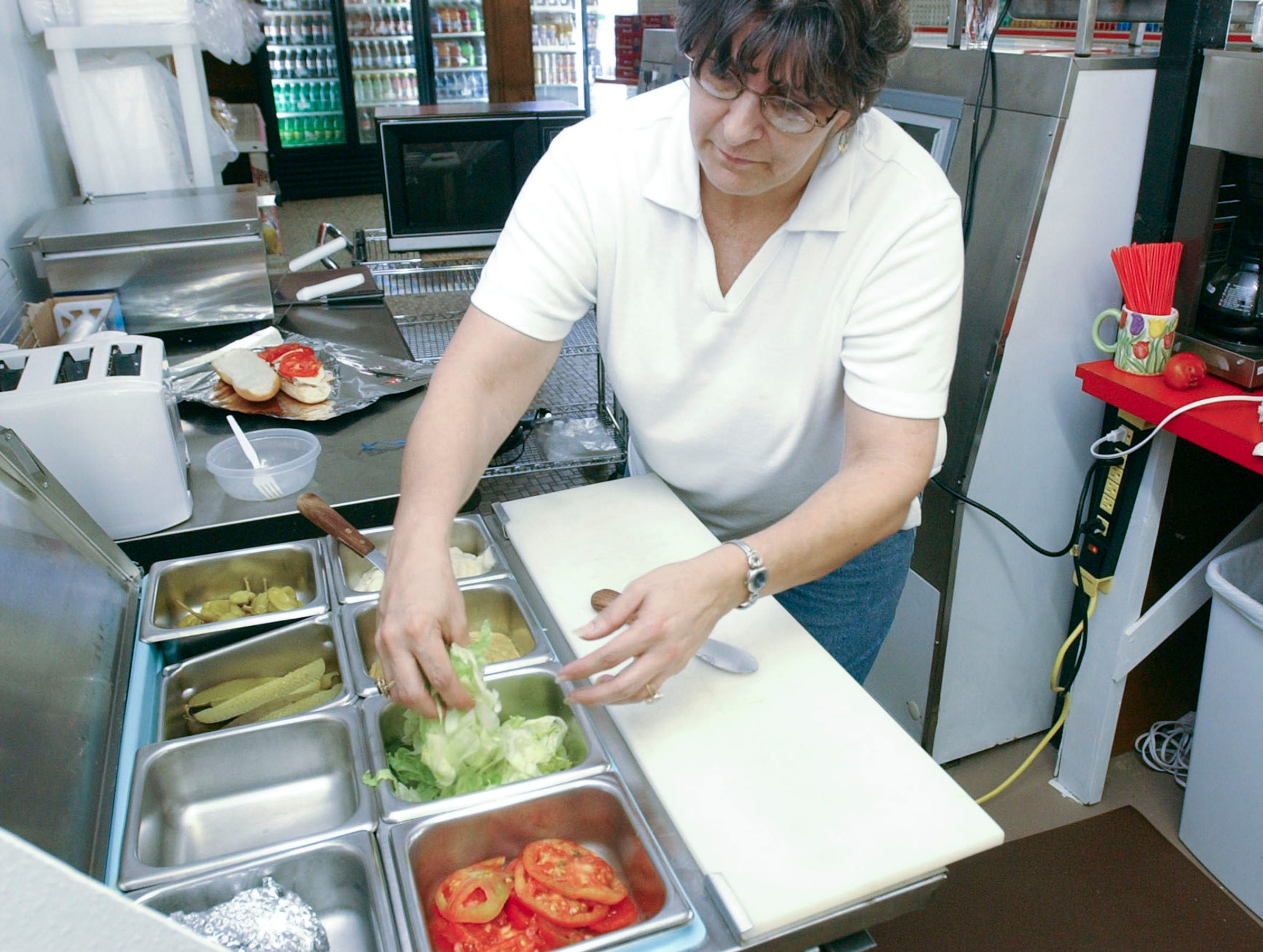 Gail Carmichael prepares a sandwich for a customer at the new North Fifth Avenue Deli and Market in 2003. The Carmichael's have completely remodeled an old bar into a market and deli.