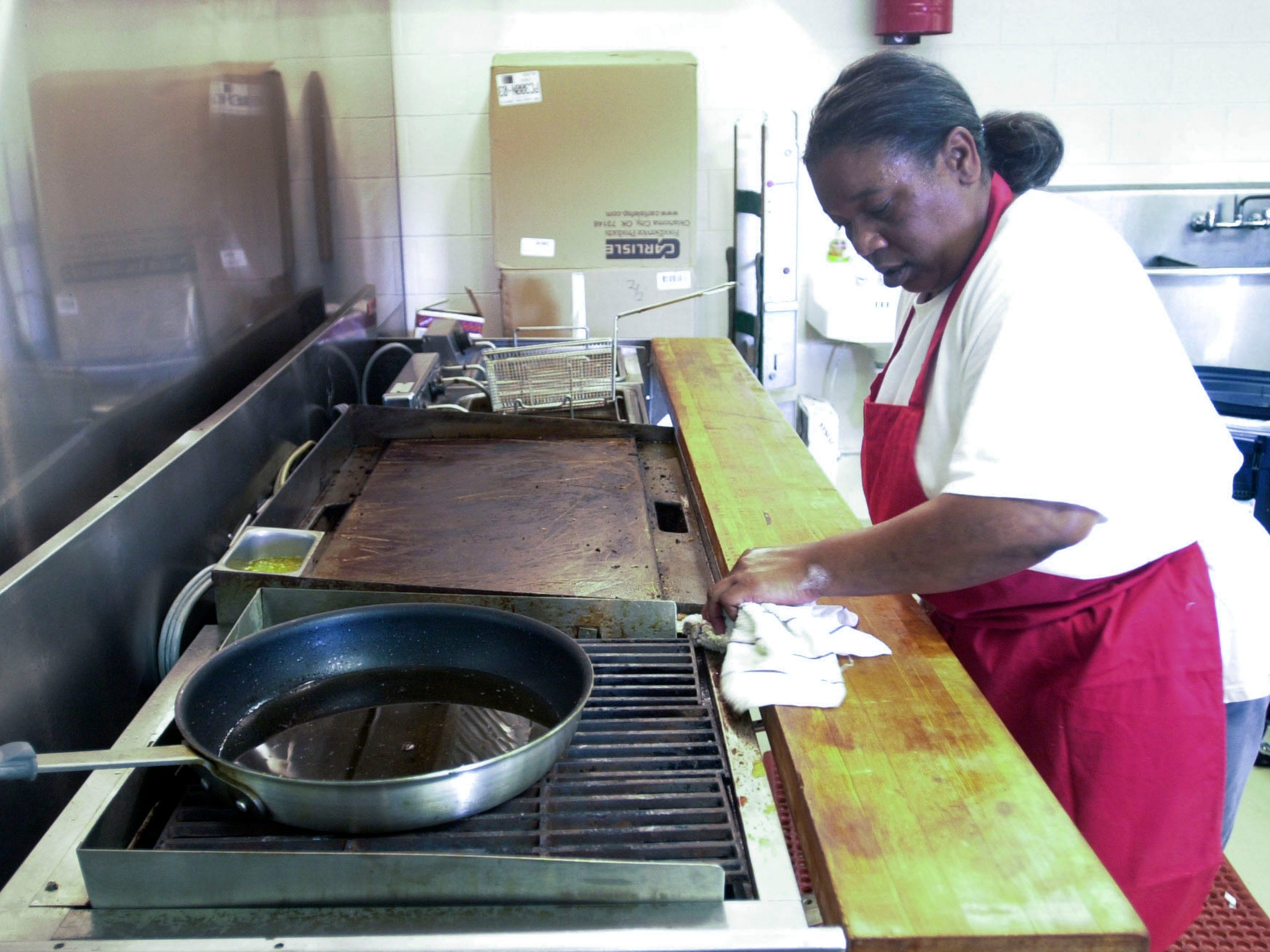 Nedra Gray, head chef at the Cajun Cafe, cleans up after a series of orders during the opening day of business in 2003.