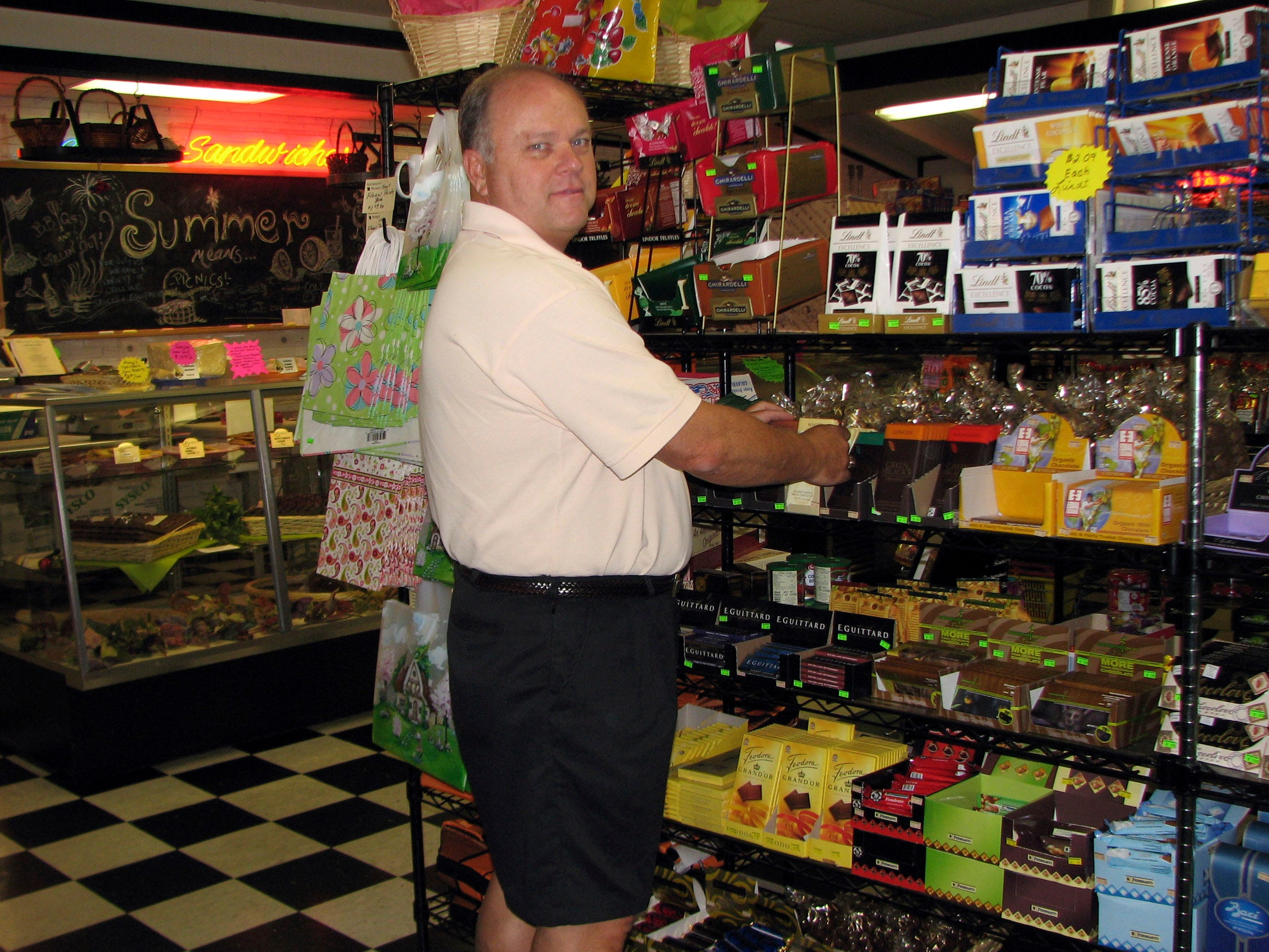 Manager Greg Locke shelves some of the 300 plus chocolate bars at Gourmet's Market in Bearden. The bakery cases and cafe are in the background in 2006.