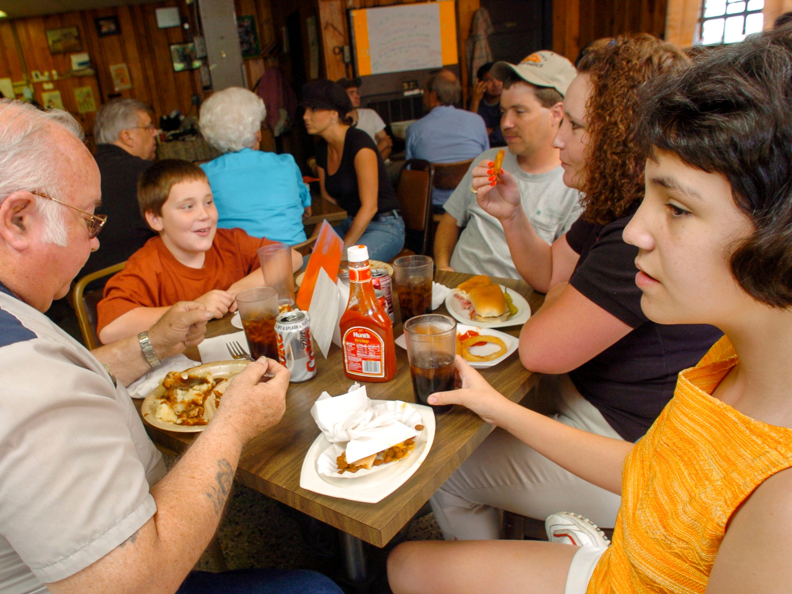 John Ford, left, has lunch with Ronnie and Heather Collins, center, and their children Nicole, 11, right, and Brandon, 9, at the Glenwood Sandwich Shop Thursday, June 3, 2004 in the Fourth and Gill neighborhood. The restaurant will close it's doors after 61 years of business.