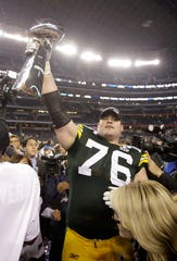 Green Bay Packers' Chad Clifton holds up the Vince Lombardi Trophy as he and his teammates celebrate the Packers' 31-25 win against the Pittsburgh Steelers after the NFL football Super Bowl XLV game on Sunday, Feb. 6, 2011, in Arlington, Texas.