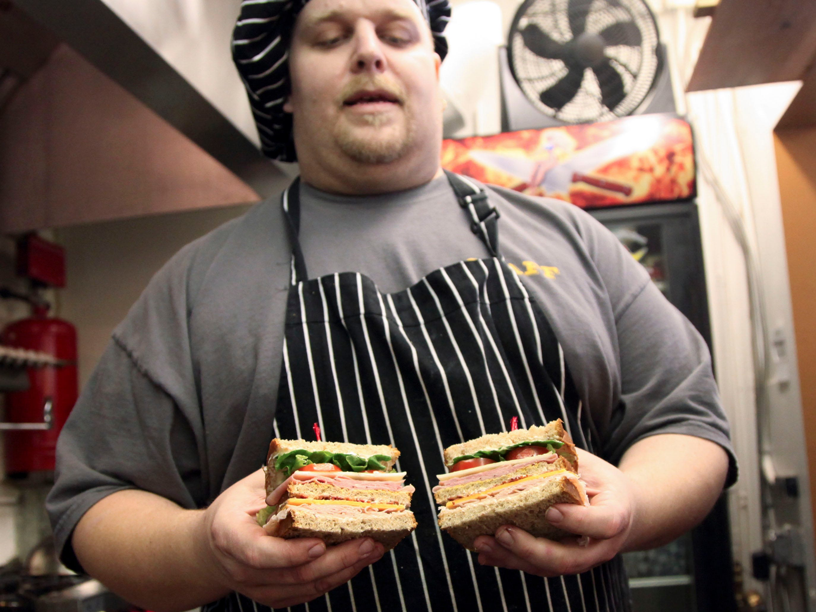 Josh Headrick holds a King of Clubs sandwich that hasturkey, ham, cheese and bacon at Mrs. Goodstuff's Cafe on E. Woodland Ave. Friday, Jan. 8, 2010.