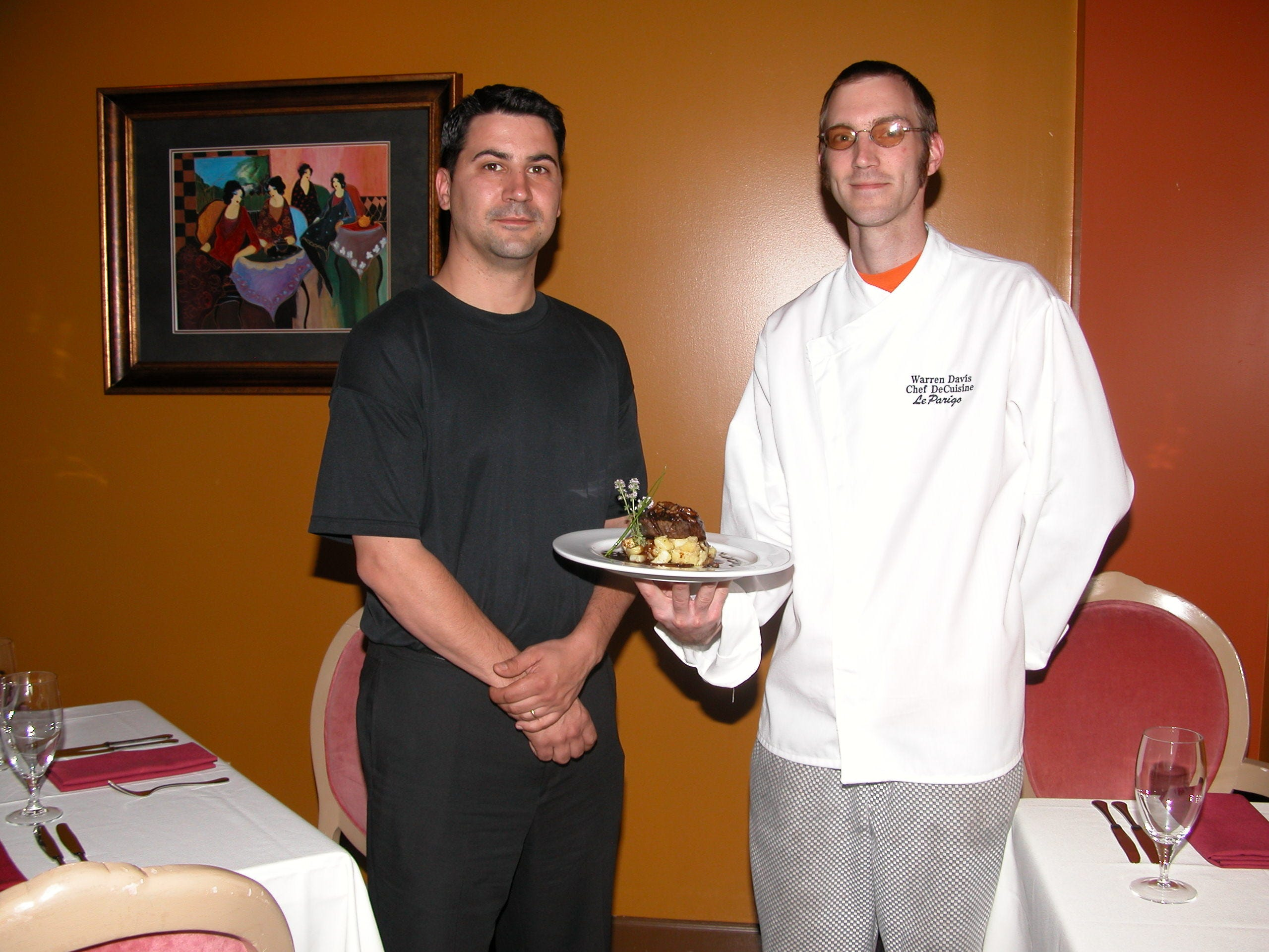 Cedric Coant, left, is the owner of Le Parigo in Bearden in 2006. At right is Chef Warren Davis with a newly prepared filet mignon.