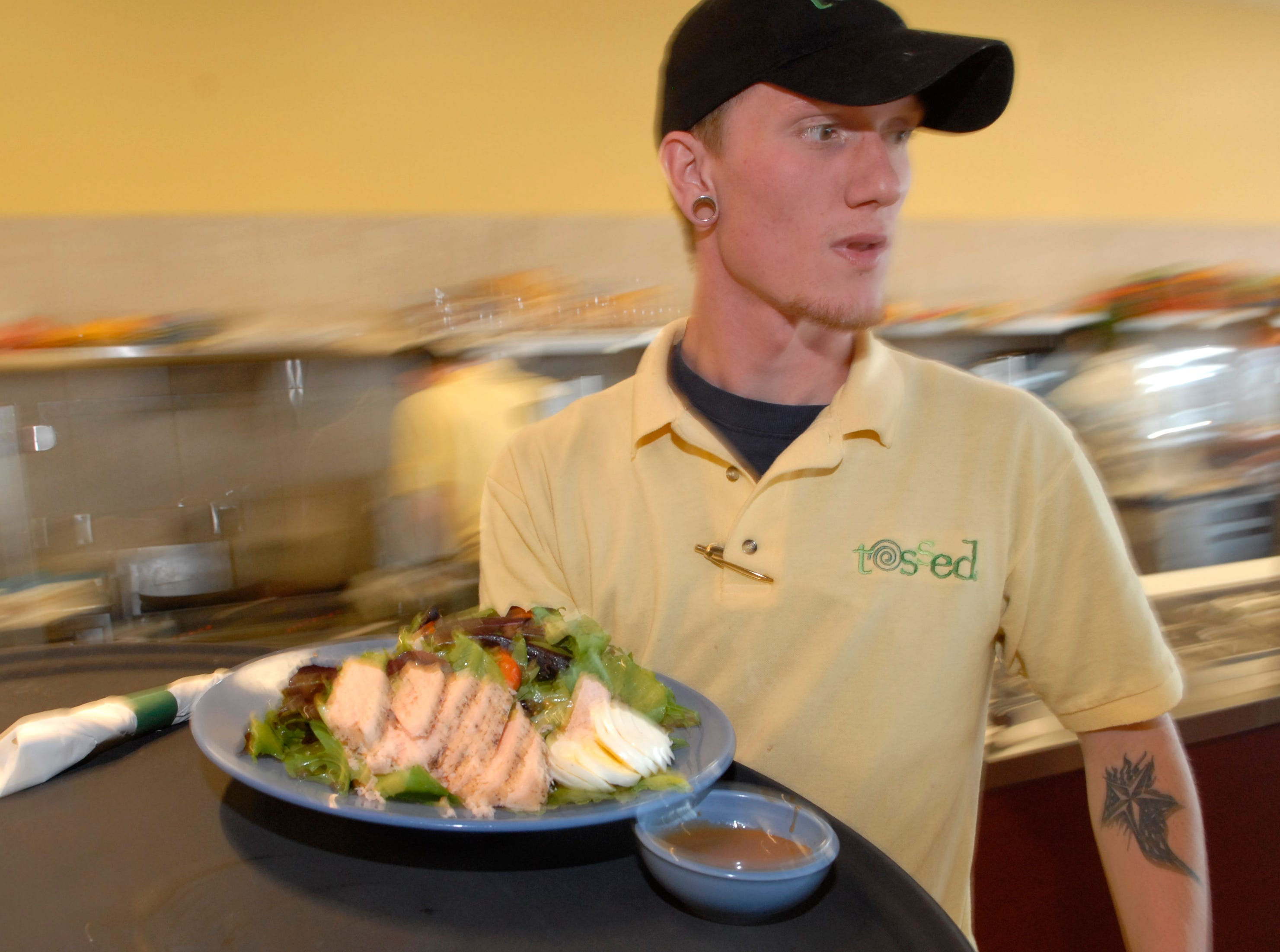 Tossed employee Tennessee Smith delivers a meal to a table on Thursday, March 3, 2007 at the new restaurant in Turkey Creek. The restaurant specializes in salads, crepes and sandwiches made to order with customers choosing from 100 ingredients.