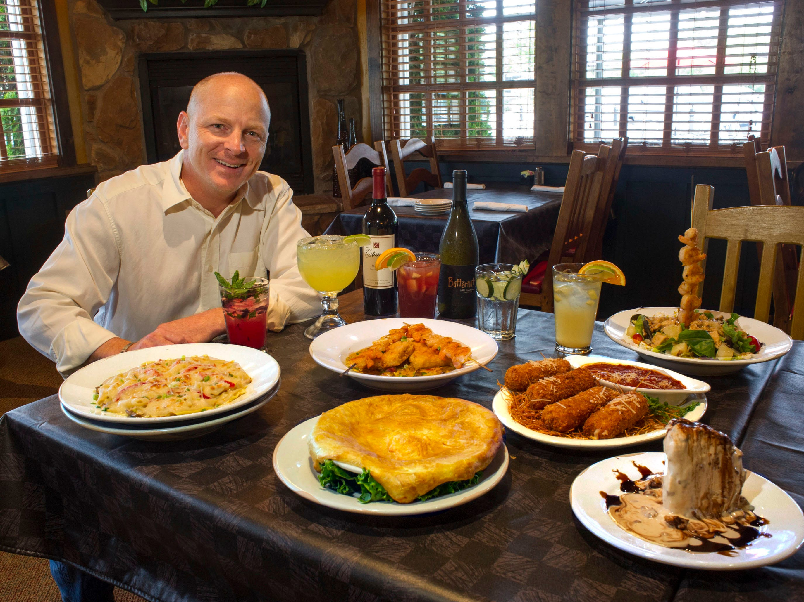 New Silver Spoon owner Dave McFarland shows off some menu choices on Tuesday, July 2, 2013, at the West Knox County restaurant.