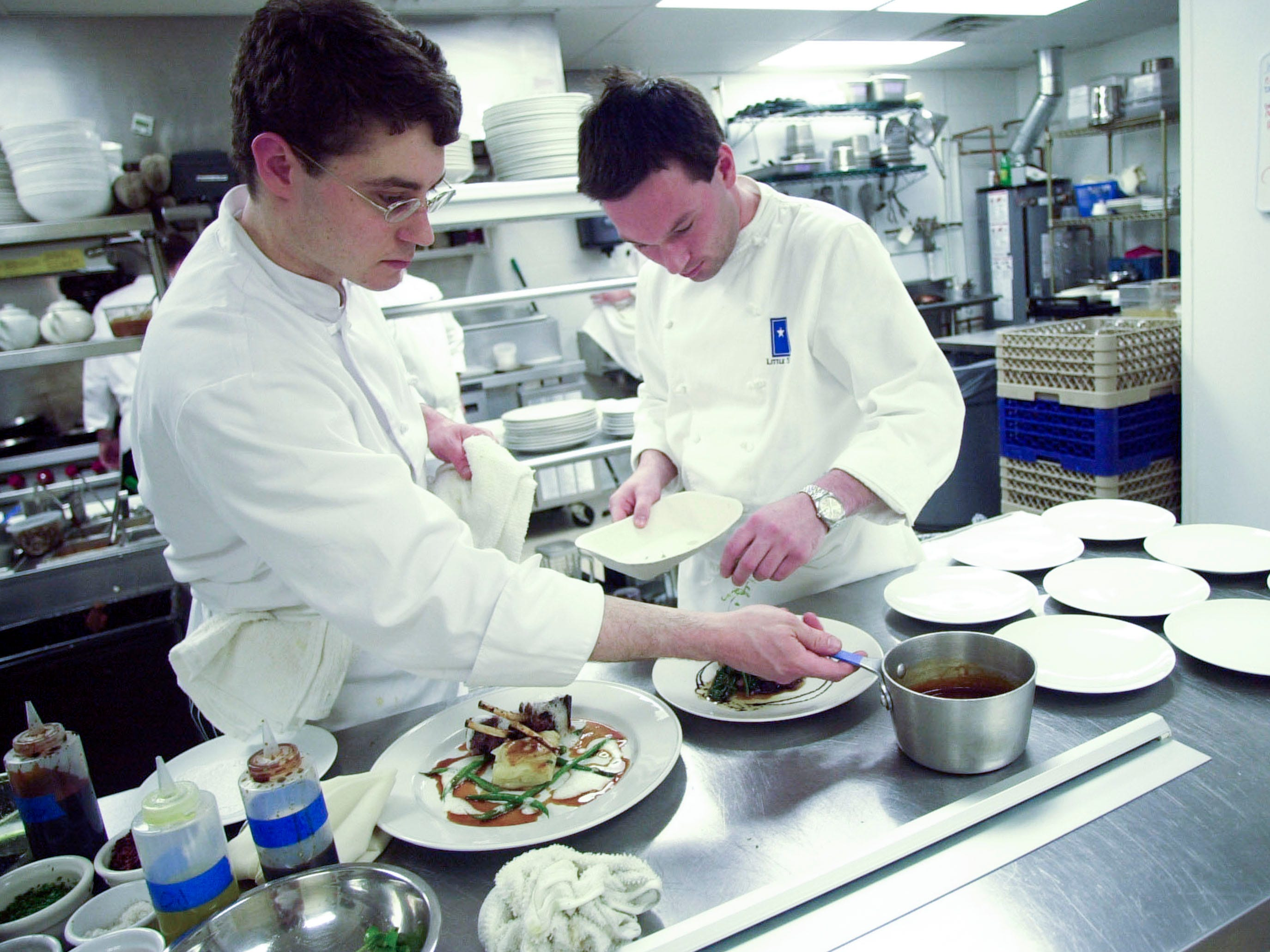 Little Star owner John McKee, right, and executive chef Chris Stallard put finishing touches on dishes ready to be served in 2003.