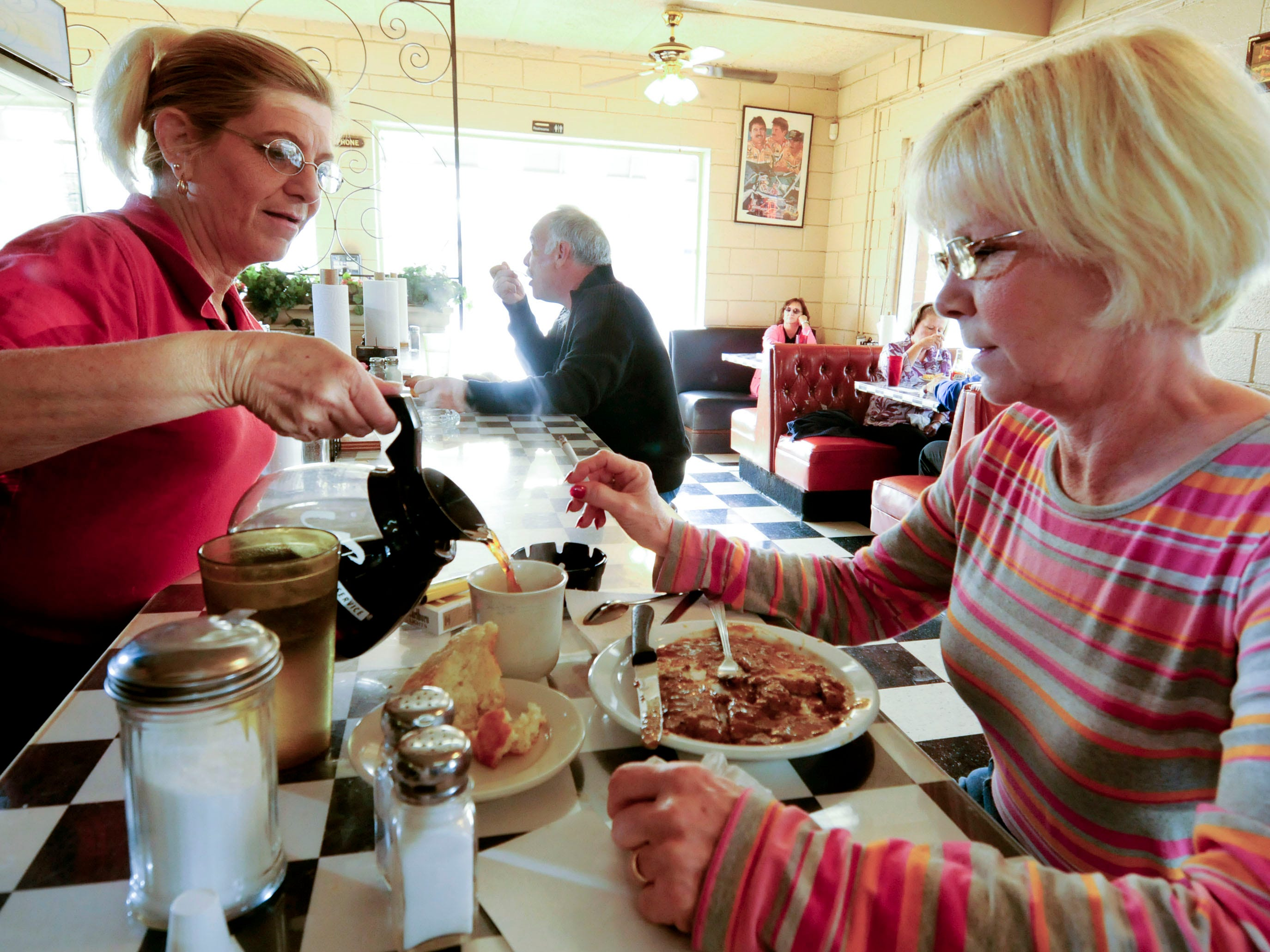 It's been a year since Tennessee outlawed smoking in restaurants and West Haven Restaurant is doing better business after the law. Customer Penny Howe, right, enjoys a cigarette with coffee served by Pattie Smith in 2008.