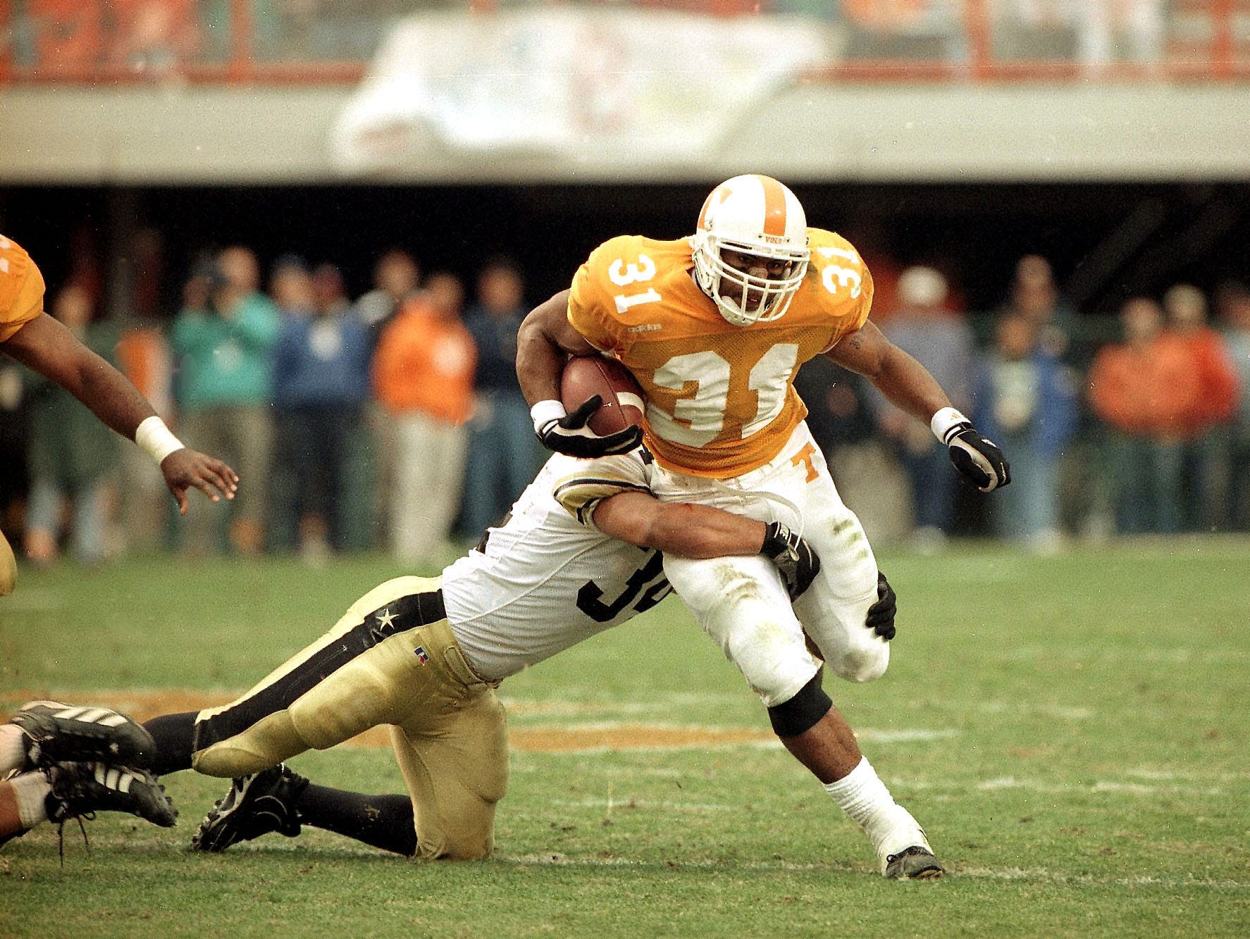 Tennessee's Jamal Lewis is grabbed by Vanderbilt's Carlton Hall in January 31, 1997.