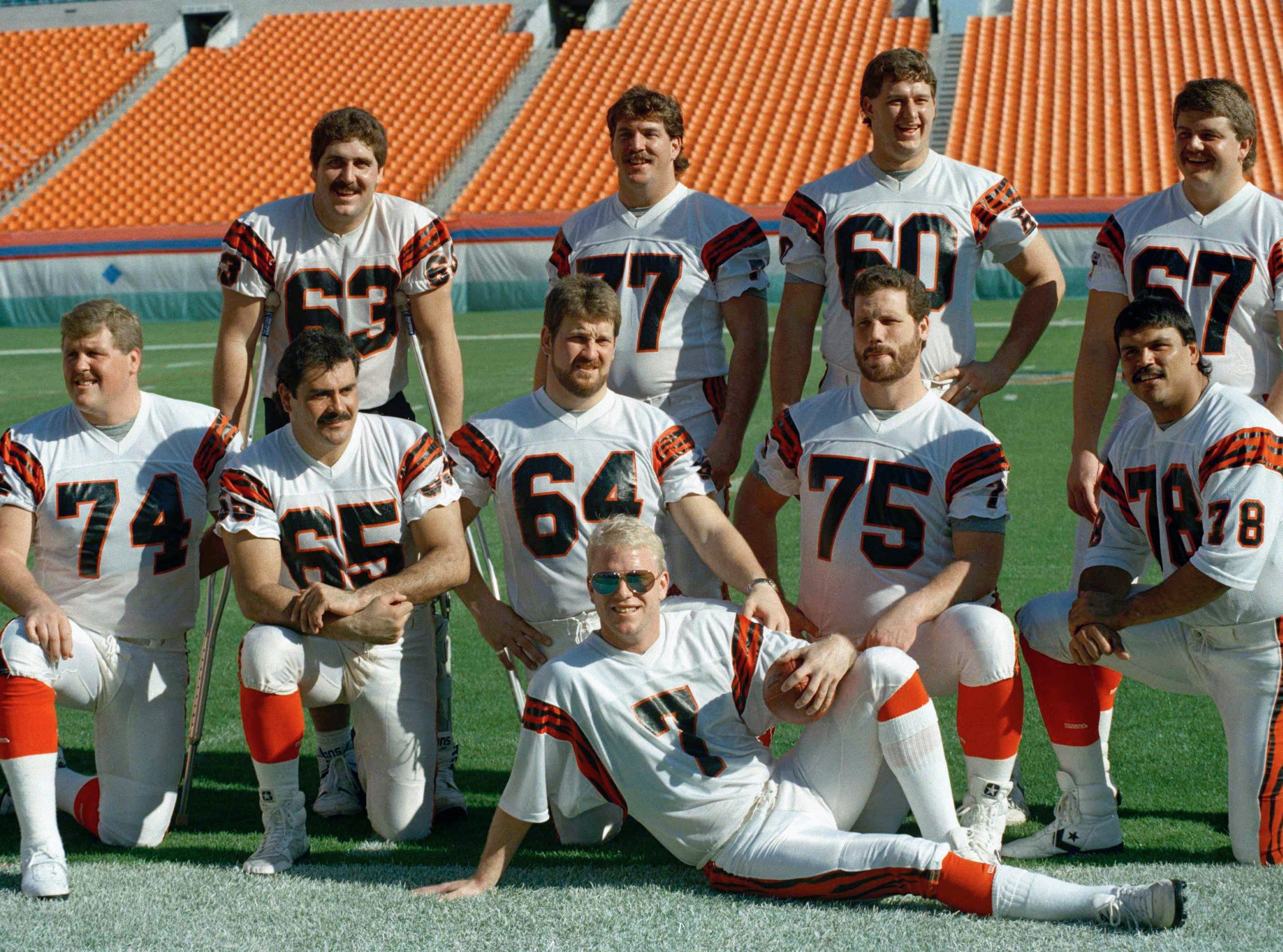 Cincinnati Bengals quarterback Boomer Esiason (7) poses with the Bengals' offensive line in Miami as they turn out for Super Bowl Media Day on Tuesday, Jan. 17, 1989. From left, back row: Joe Walter (63), Herb Wester (77), Dave Smith (60), David Douglas (67). Front: Brian Blados (74), Max Montoya (65), Bruce Kozerski (64), Bruce Reimers (75), Anthony Munoz (78).