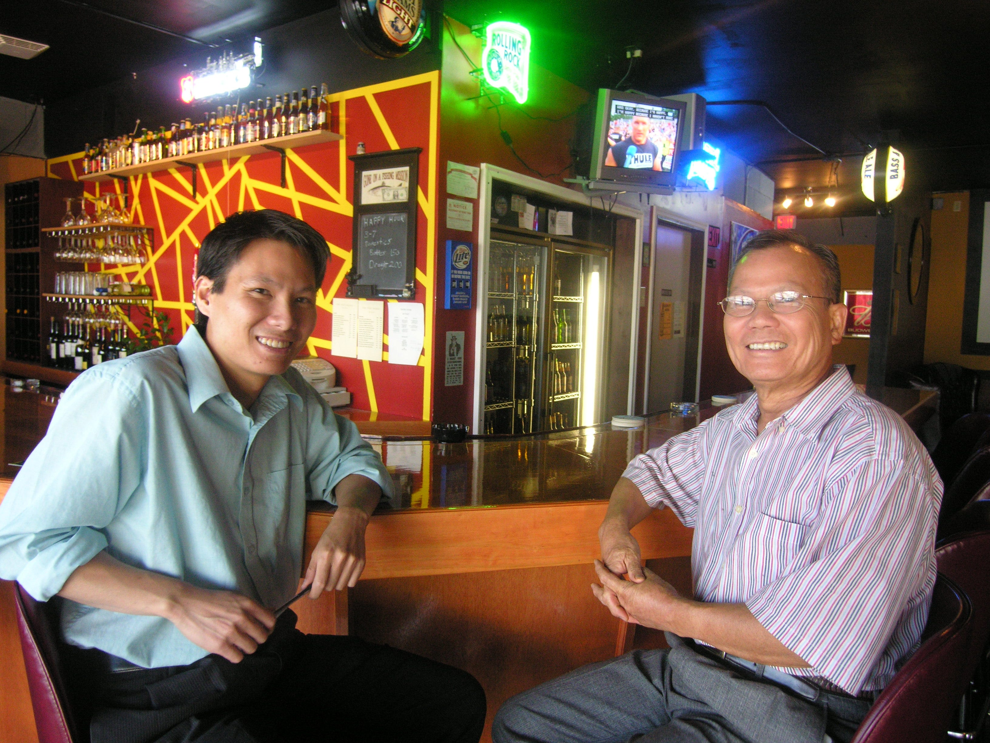 Thoai Ho, left, and his father, Thanh Ho, sit at the bar of the Pint House in 2006. The Ho family opened the establishment next to their T. Ho Bistro restaurant on Merchant Drive. Thoai Ho says the Pint House is a neighborhood pub, but with a menu of Vietnamese food.