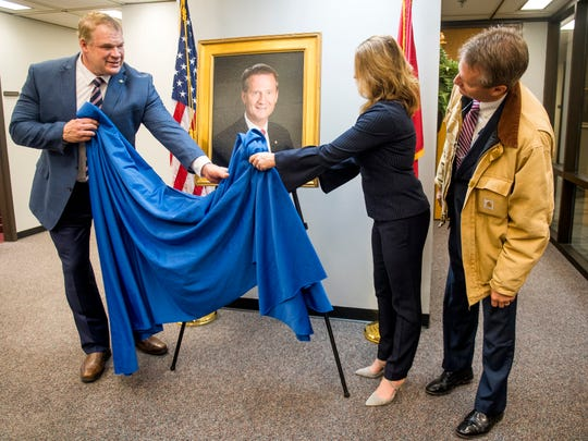 Former Knox County Mayor and current Congressman-elect Tim Burchett, right, peers over at his portrait as Knox County Mayor Glenn Jacobs, left, and Burchett's wife Kelly finish unveiling it Friday.