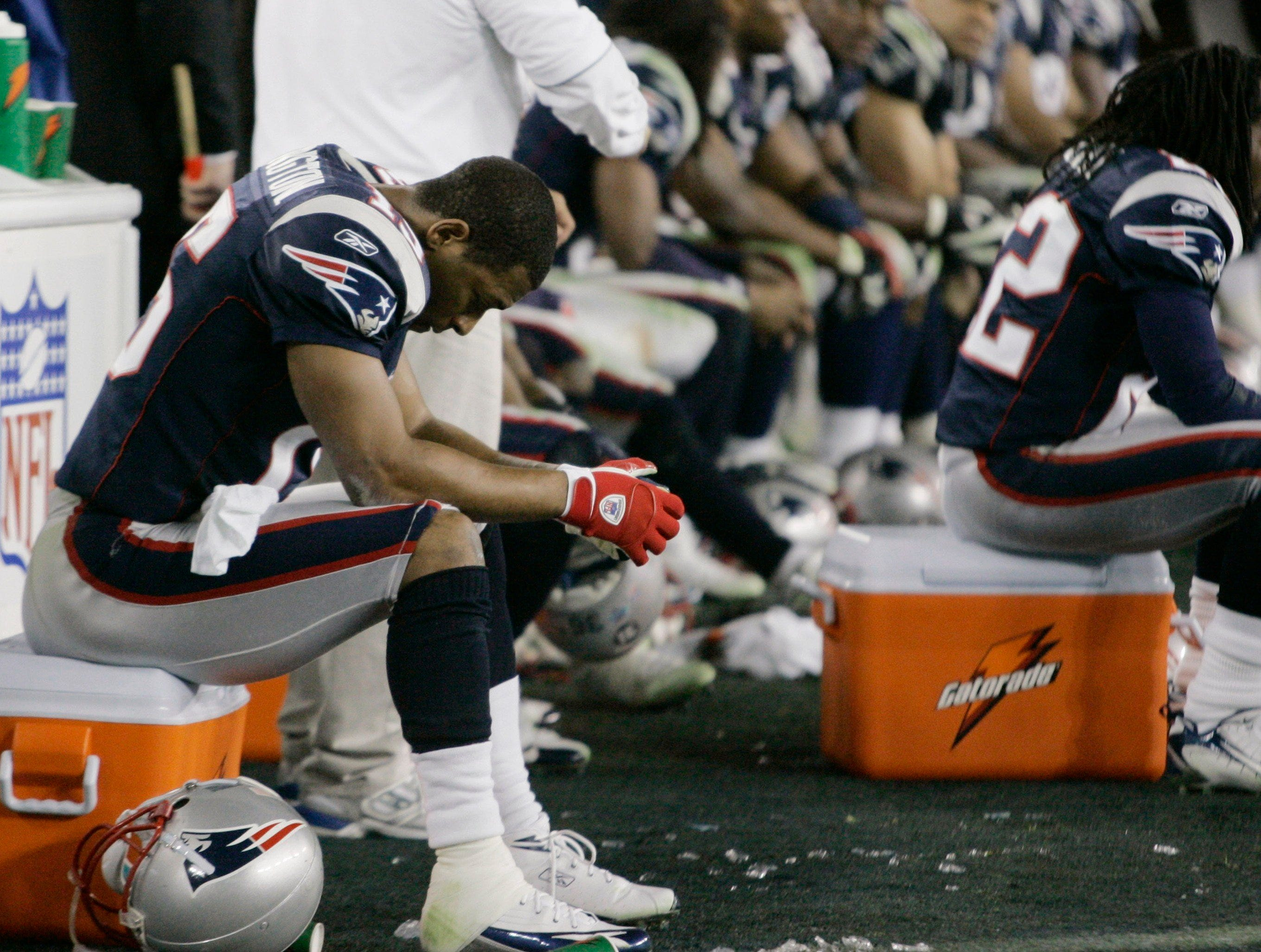 New England Patriots receiver Kelley Washington, left, sits on the bench with his teammates after the Patriots lost to the New York Giants 17-14 in the Super Bowl XLII football game on Sunday, Feb. 3, 2008, in Glendale, Ariz.