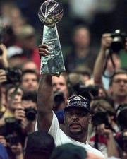 Green Bay Packers' Reggie White carries the Lombardi Trophy after beating the New England Patriots 35-21 to win Super Bowl XXXI Sunday, Jan. 26, 1997, in New Orleans.