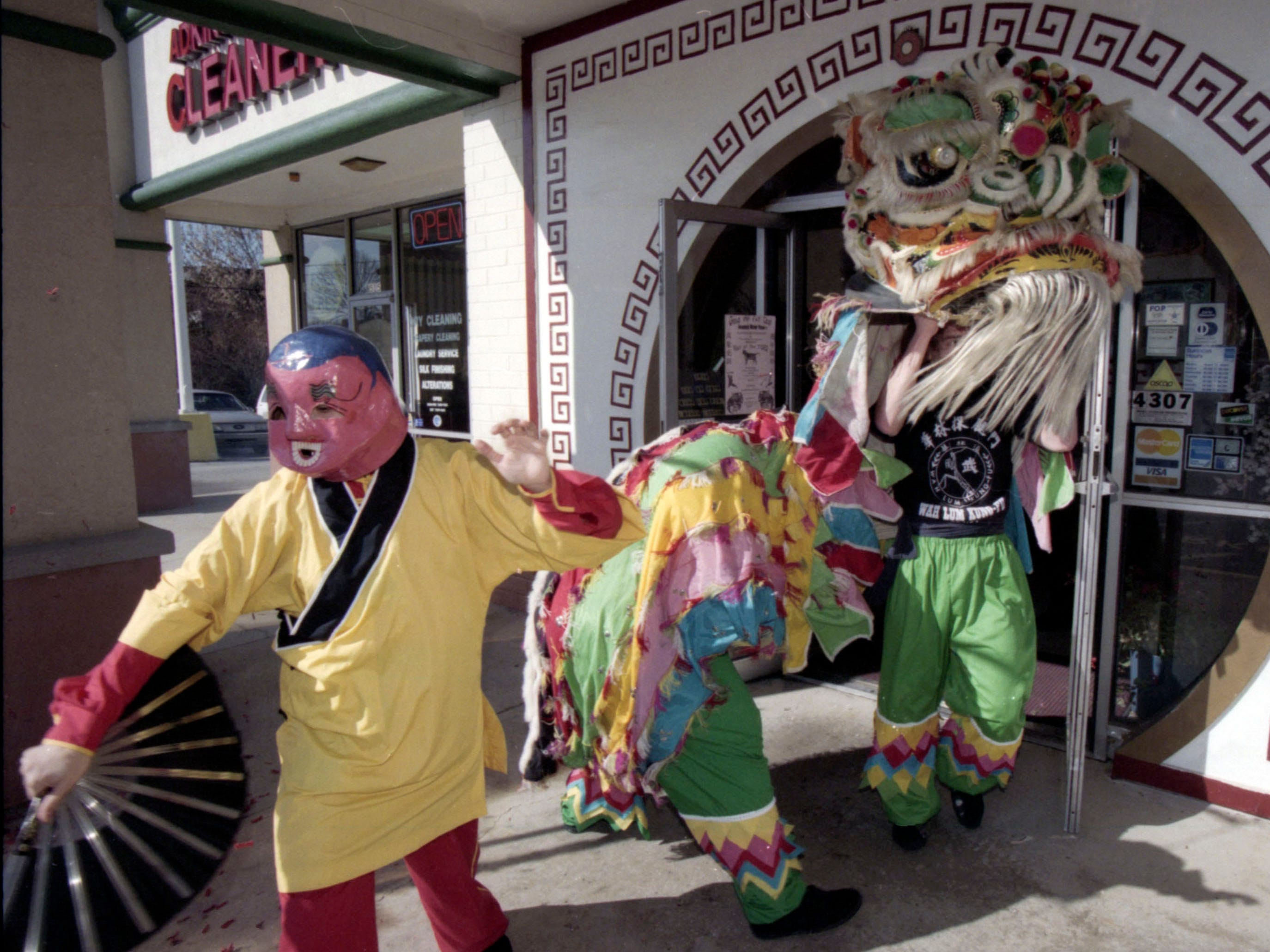 Marian Allen, left, leads a dragon out the front doors of Canton Restaurant in West Knoxville during a Chinese New Year celebration in 1998.