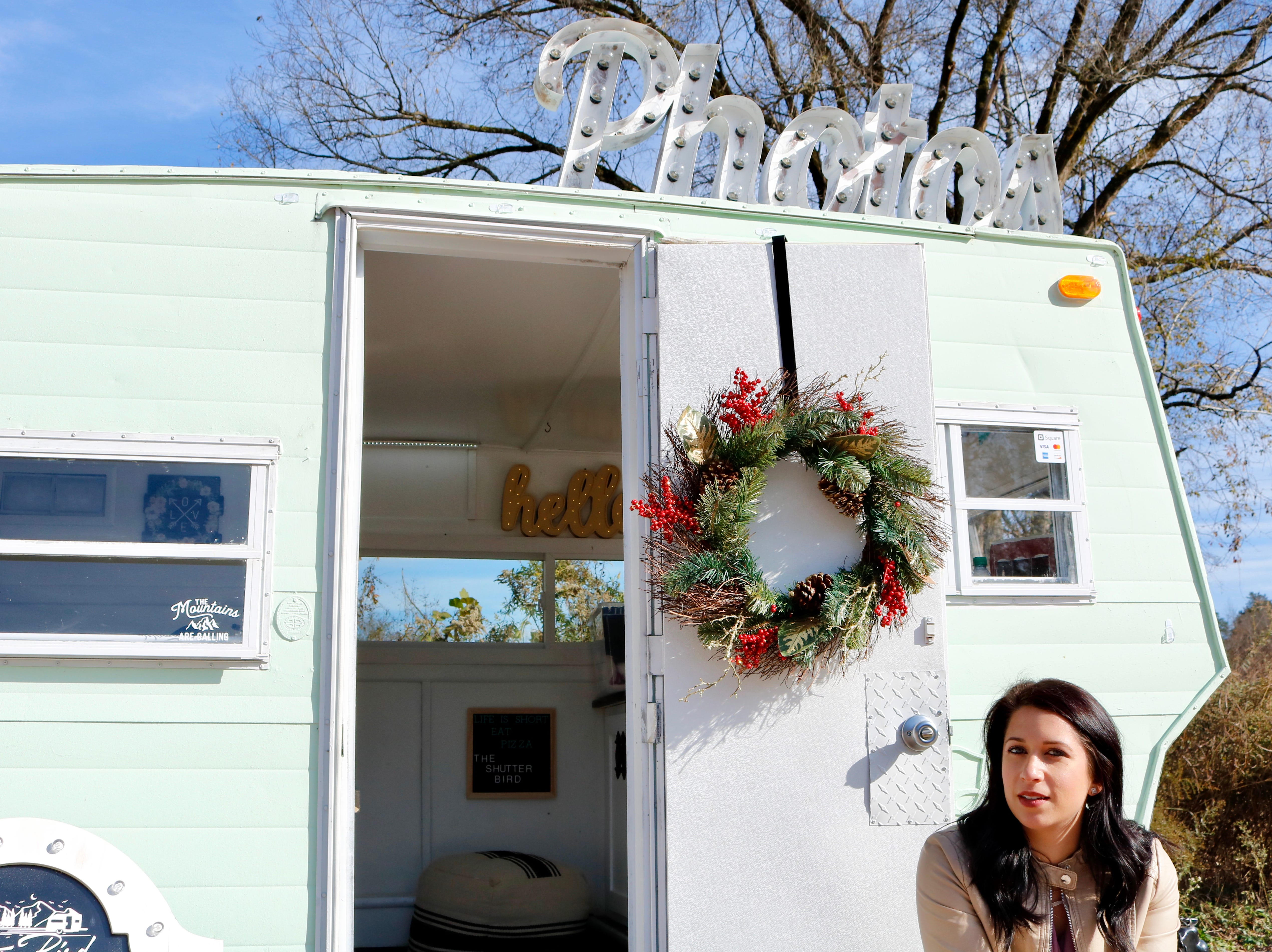 "Amanda Irizarry sits on the steps of her 1970s Lark vintage camper, turned Shutter Bird Photo Camper. ""Hearing about a mobile photo booth might be hard to fully understand, it's good for people to see it and see how it works,"" she said."