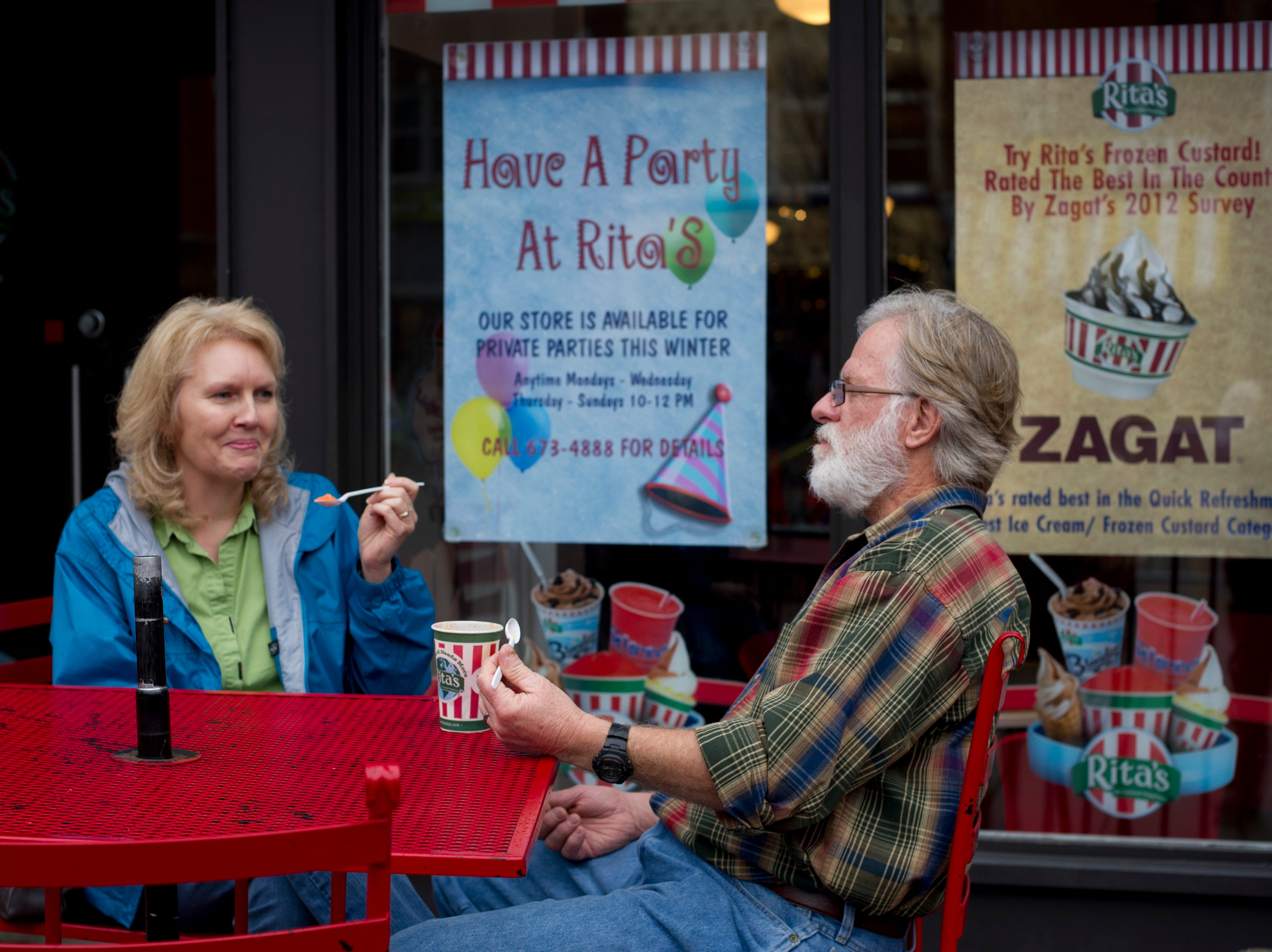 Lisa Bean and her husband Ron Bean take in the unseasonably warm weather with a cup of Italian Ice outside of Rita's at Market Square on Sunday, January 13, 2013.