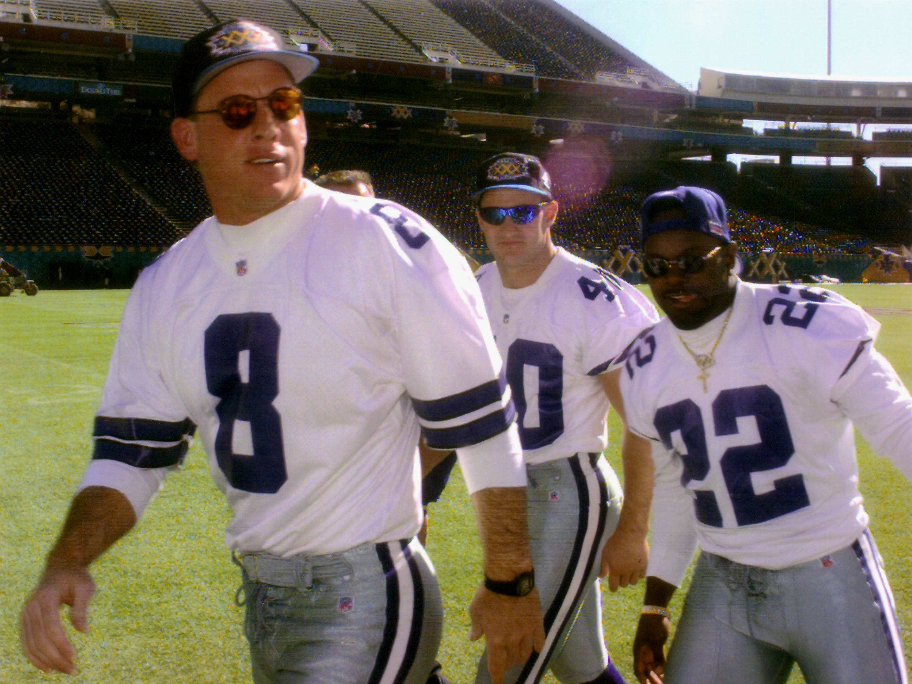 Dallas Cowboys quarterback Try Aikman, left, safety Bill Bates and running back Emmitt Smith, right, head for the team bus after Super Bowl XXX Media Day activities in Tempe, Arizona, Jan. 23, 1996.