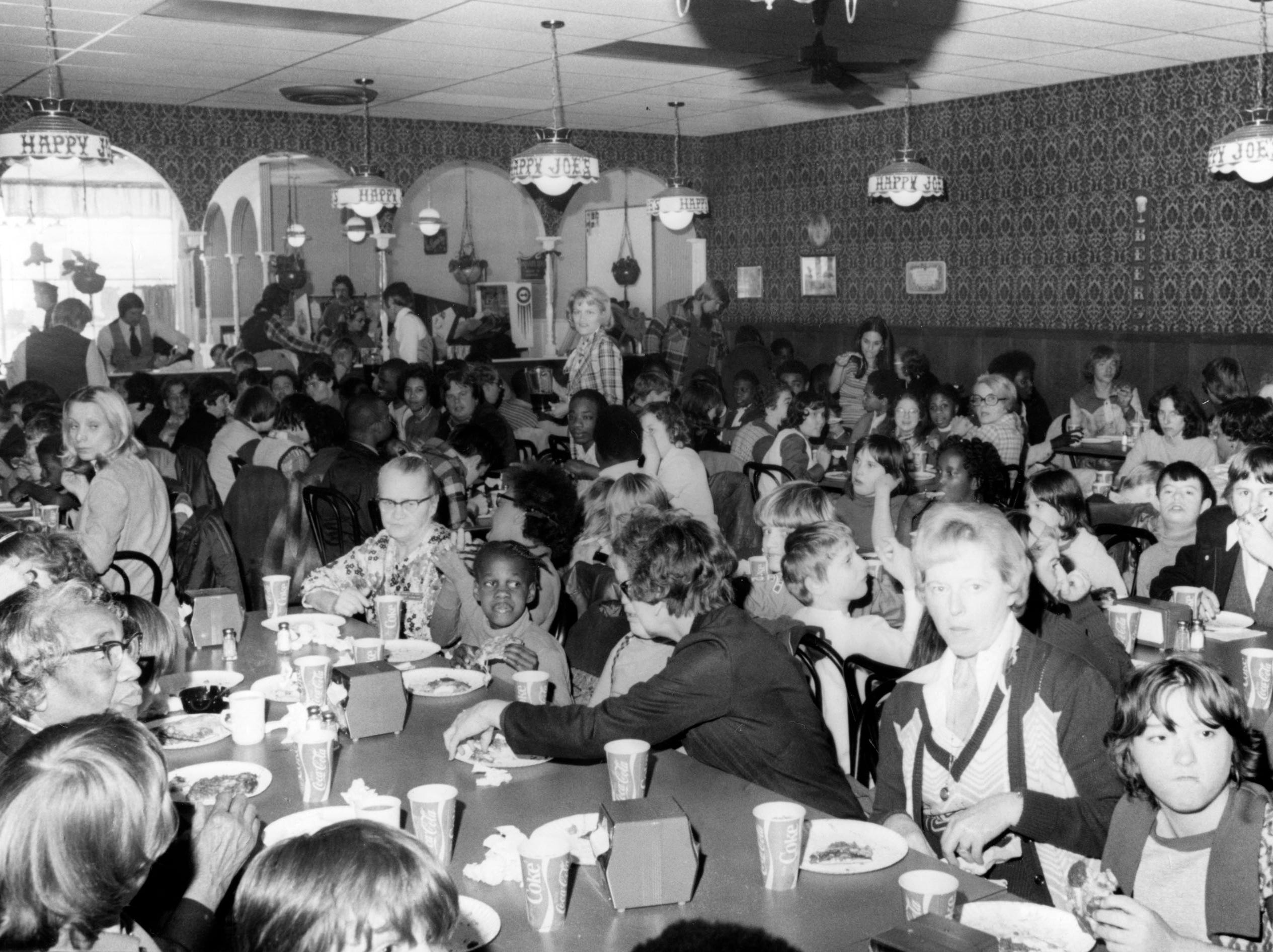 About 300 children from special education centers were treated to free pizza, ice cream, and soft drinks at Happy Joe's Old Fashioned Pizza and Ice Cream Parlor at 2907 Tazwell Pike in December 1976.