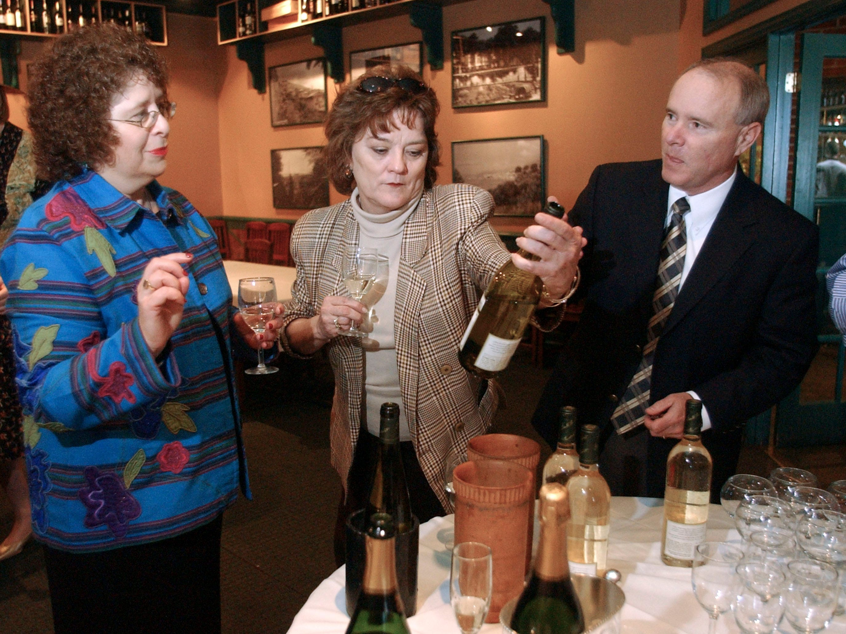 From left, Millie Hetrick, Bettye Sisco, and Jim Varnado  talks about the wine produced and bottled at Biltmore Estate Winery during a tasting at Italian Market & Grill in 2004.