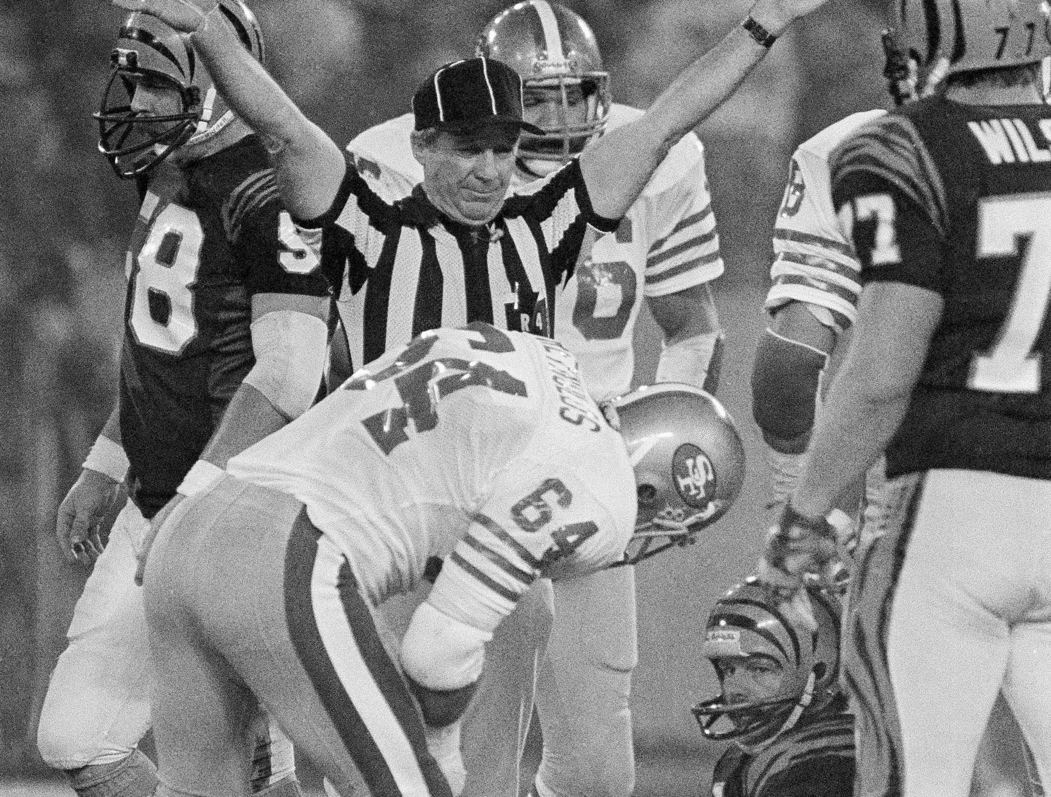 Cincinnati Bengals quarterback Ken Anderson (14) gets a word from San Francisco 49ers linebacker Jack Reynolds (64) after being sacked in the third quarter, Sunday, Jan. 25, 1982 in the Pontiac Silverdome.