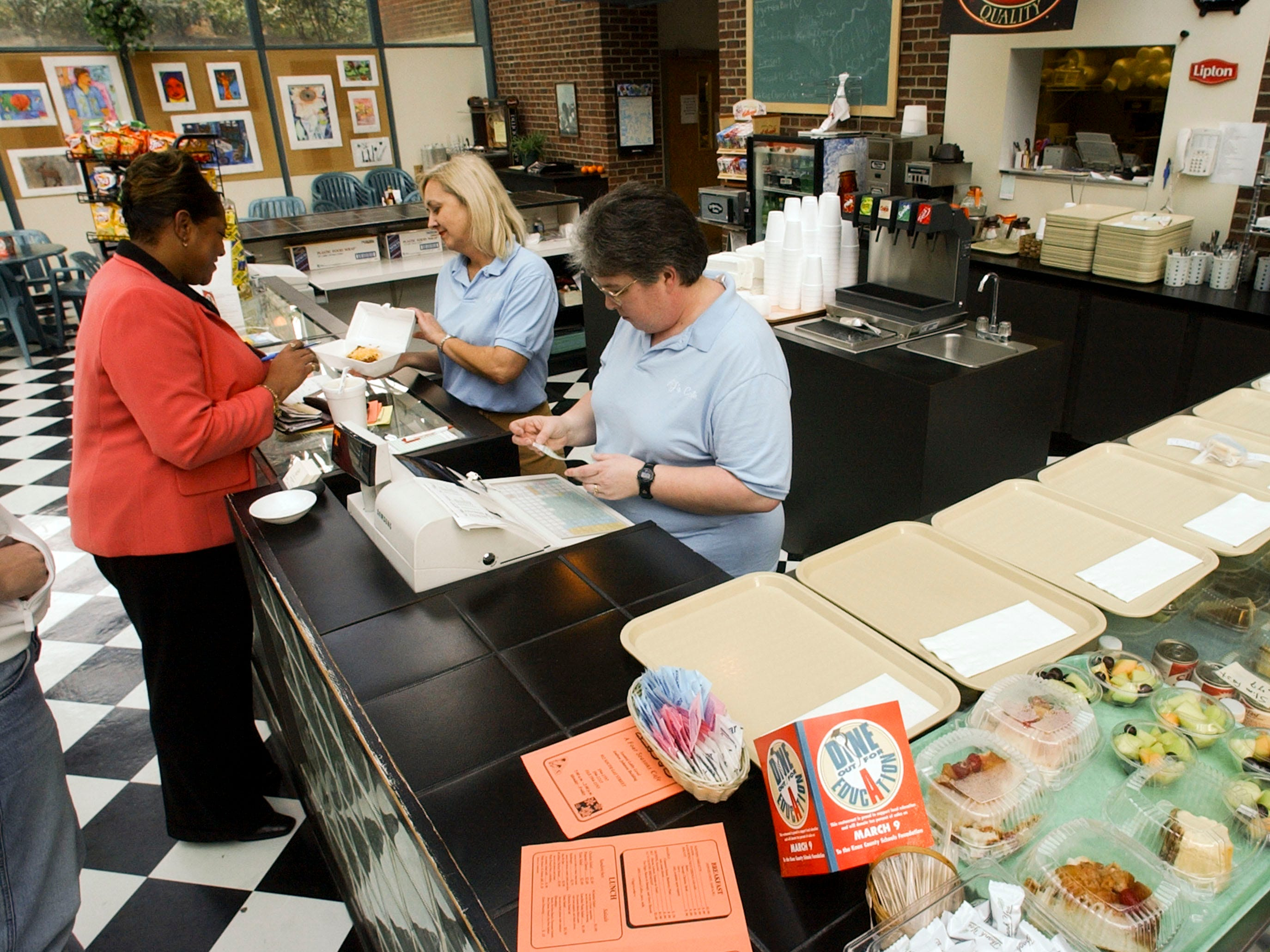 in 2004, A.J.'s a four seasons cafe located off the lobby of the Andrew Johnson Building, is one of  many Knoxville restaurants participating in the Dine Out Day find raising for Knox County School. Customers Sharon Upshaw picks up her lunch order from A.J.'s manager Darlene Harvey while assistant manager Laura Bennett works the cash register.