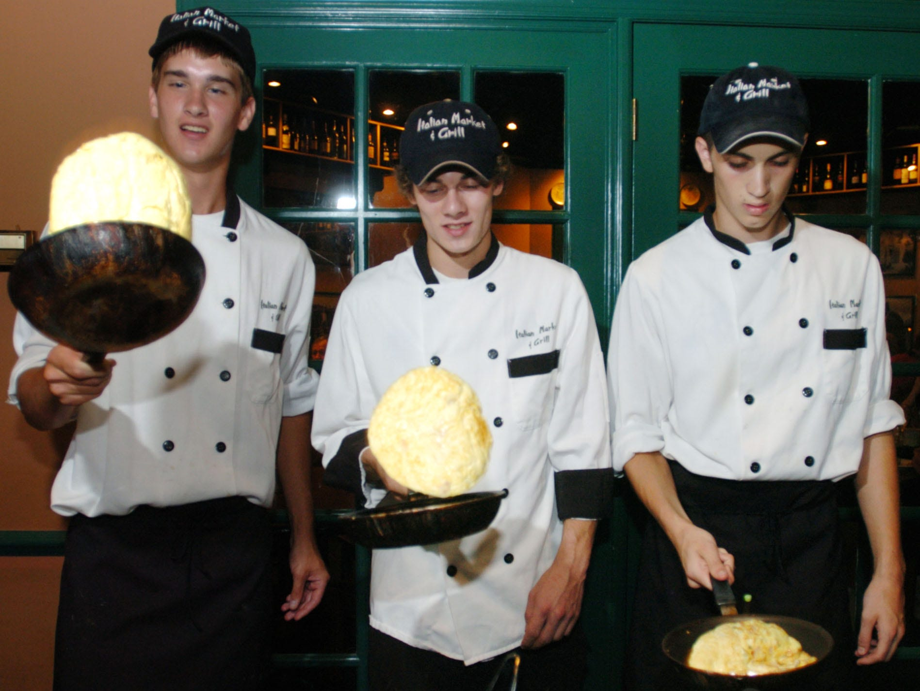 From left Tom Sawyer, Clint Lensgraf, and Nick Carideo cook and flip omelets during Sunday brunch in 2004 at Italian Market & Grill.