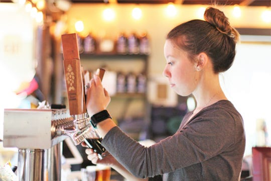 Jenn Steward pours a four ounce beer for a sampling flight at Clinch River Brewing – Norris.