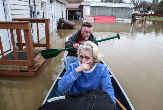 Gerald Miles paddles as Utica resident Robbin Crider holds a covered basket containing the pet cat of friend Ray Thomasson, who left the rising waters hurriedly earlier.
