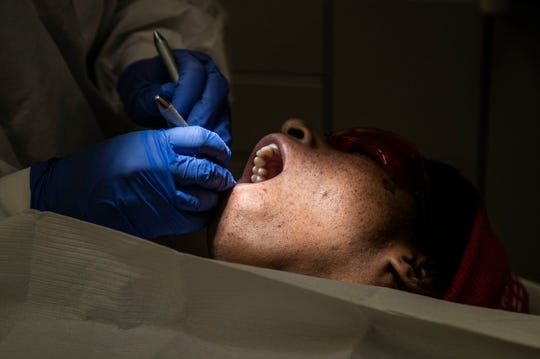 Expanded Duty Dental Assistant Darisly Rosabal works with a patient's teeth at the Family Health Center on East Muhammad Ali. Dec. 27, 2018