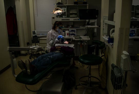 Expanded Duty Dental Assistant Darisly Rosabal works with a patient at the Family Health Center on East Muhammad Ali. Dec. 27, 2018