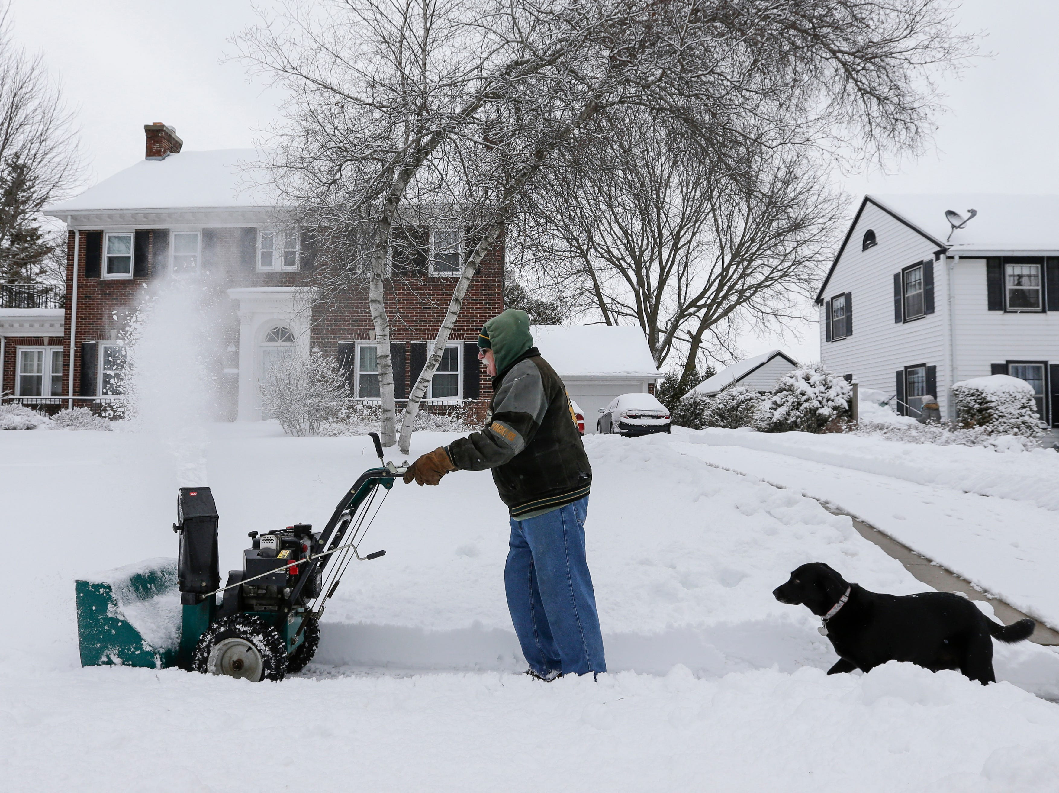 Ernie Swanson snow-blows his neighbor's sidewalk with his dog Rosie after winter storm Evelyn Monday, Apr. 16, 2018, in Manitowoc, Wis. Josh Clark/USA TODAY NETWORK-Wisconsin
