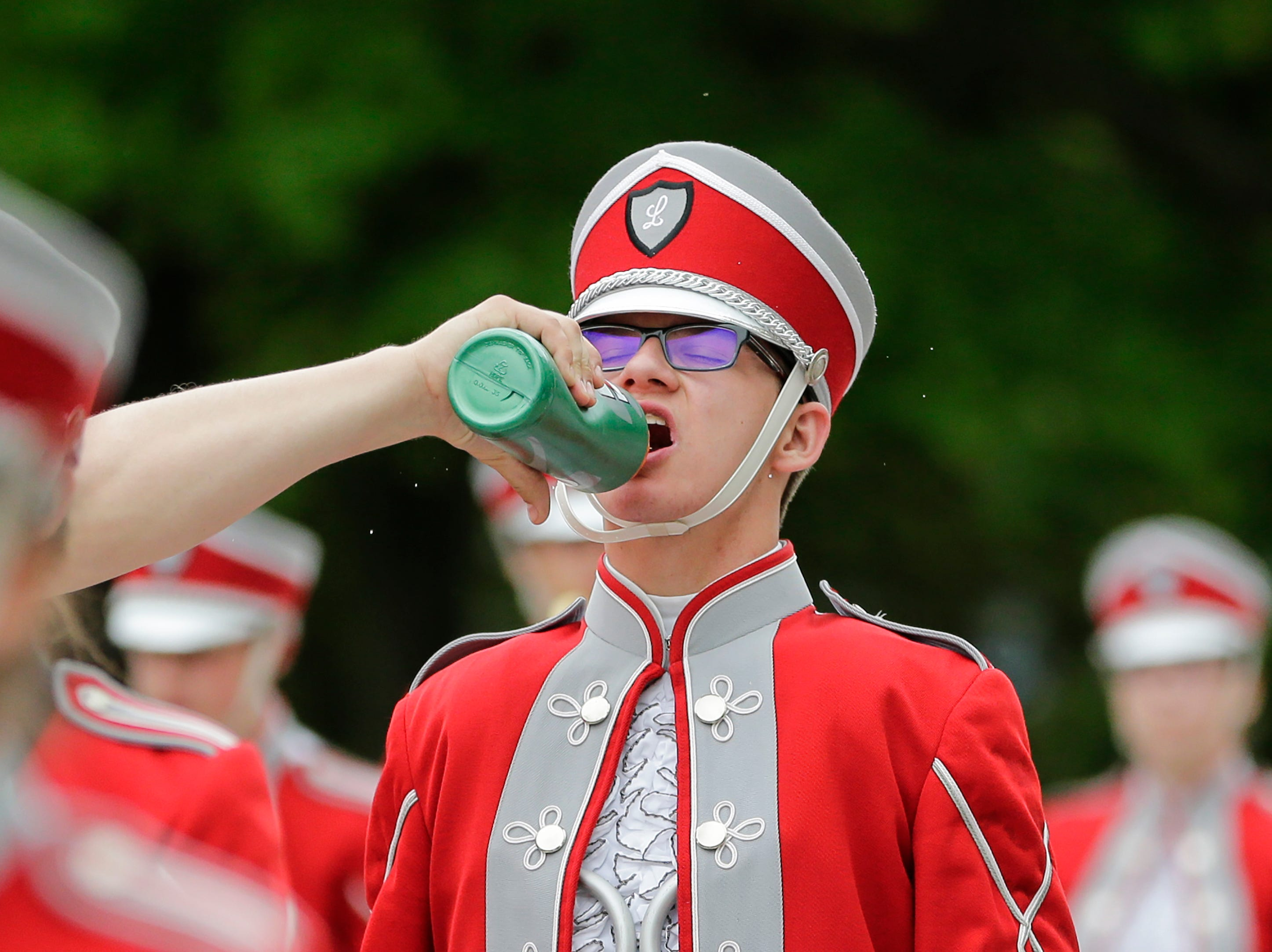 The Manitowoc Lutheran High School marching band holds for a water break during a hot and humid Memorial Day parade Monday, May 28, 2018, in Manitowoc, Wis. Josh Clark/USA TODAY NETWORK-Wisconsin