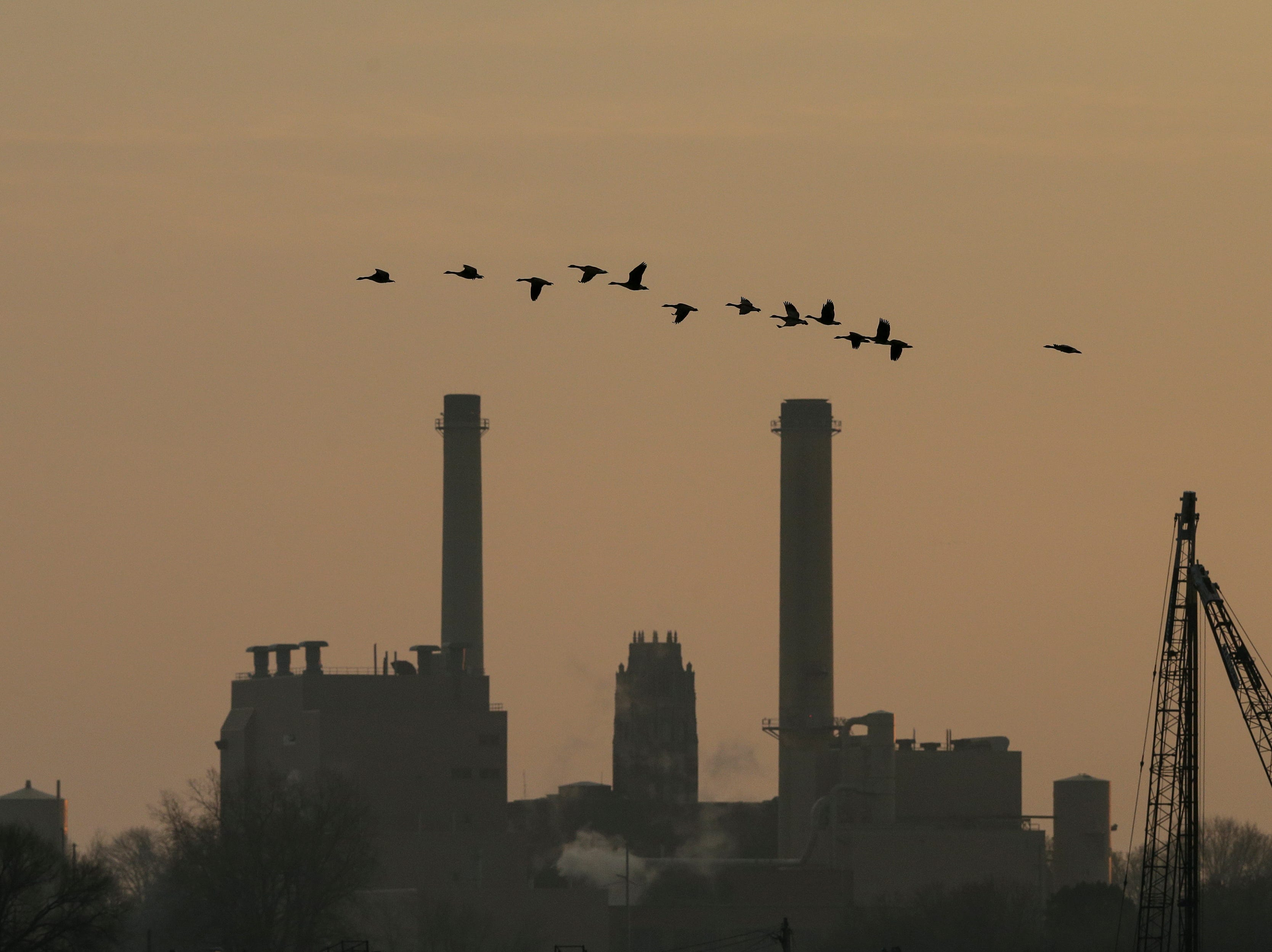 Geese fly out over Lake Michigan north of the power plant that frames Lincoln tower as the sun sets over Manitowoc, Wis., Thursday, December 13, 2018. Joshua Clark/USA TODAY NETWORK-Wisconsin