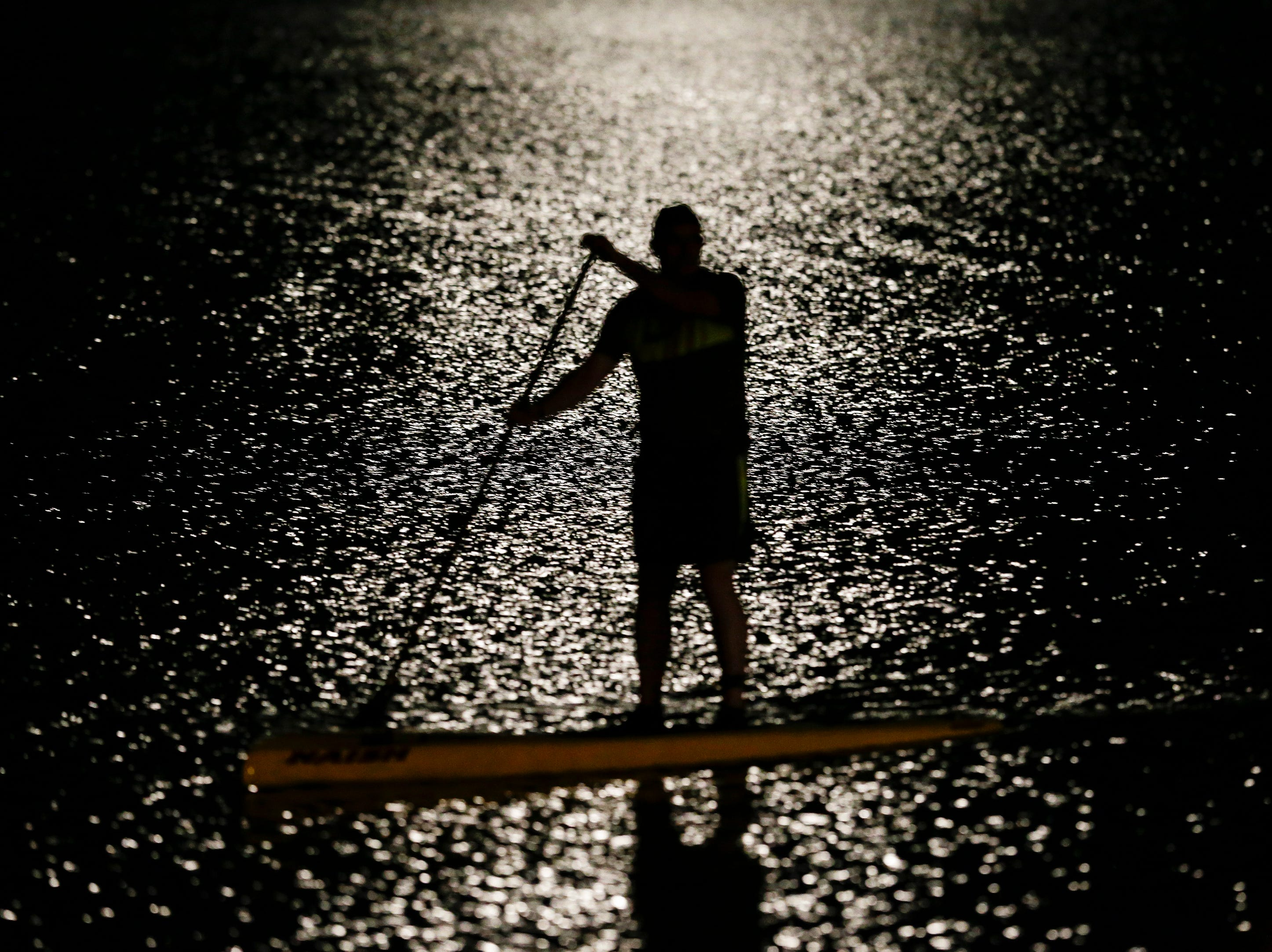 A stand-up paddle boarder is silhouetted by the full moon's reflection in Lake Michigan during a moonlight paddle Friday, July 27, 2018, in Manitowoc, Wis. Josh Clark/USA TODAY NETWORK-Wisconsin