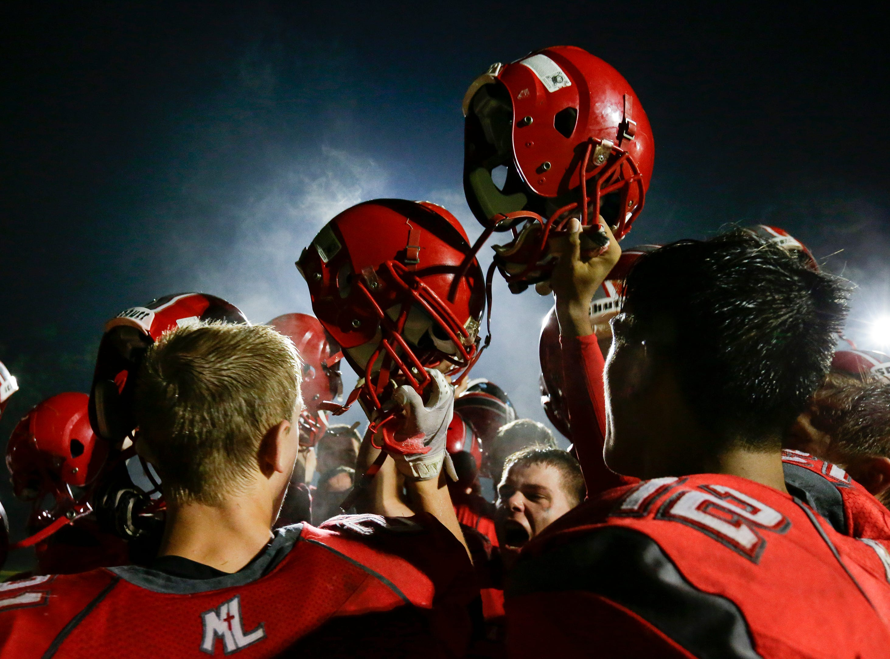Lutheran raises their helmets and sings the school song after defeating Oostburg in a Big East conference matchup 27-7 at Manitowoc Lutheran High School Friday, September 14, 2018, in Manitowoc, Wis. Josh Clark/USA TODAY NETWORK-Wisconsin
