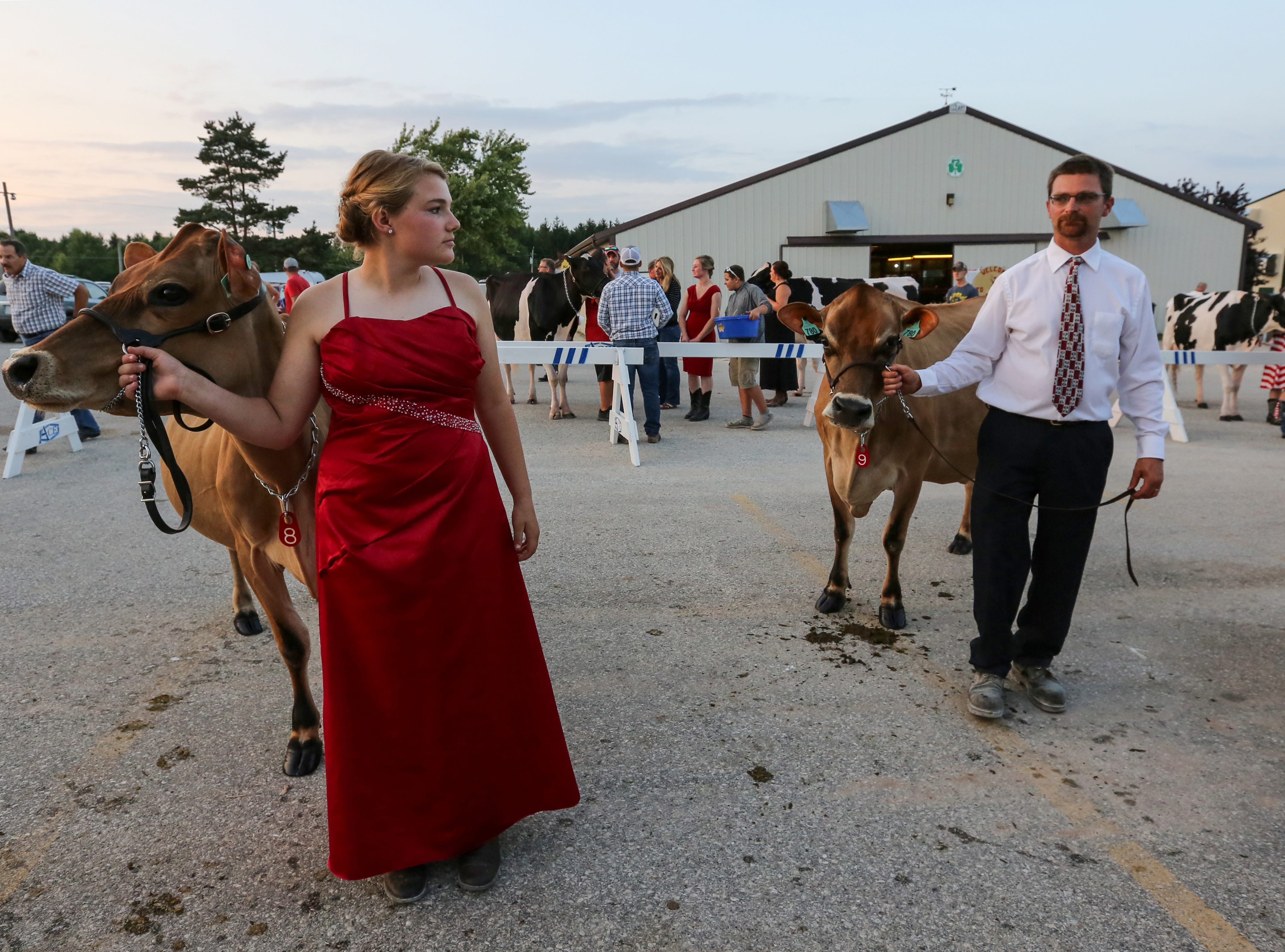 Emma and Ben Vos of Proud Heritage Jerseys in Maribel wait with their Jersey cows for their entrance during the Manitowoc Culver's Futurity at the Manitowoc County Fair Saturday, August 25, 2018, in Manitowoc, Wis. All the cows in this years' show were entered three years ago as young calves. Josh Clark/USA TODAY NETWORK-Wisconsin