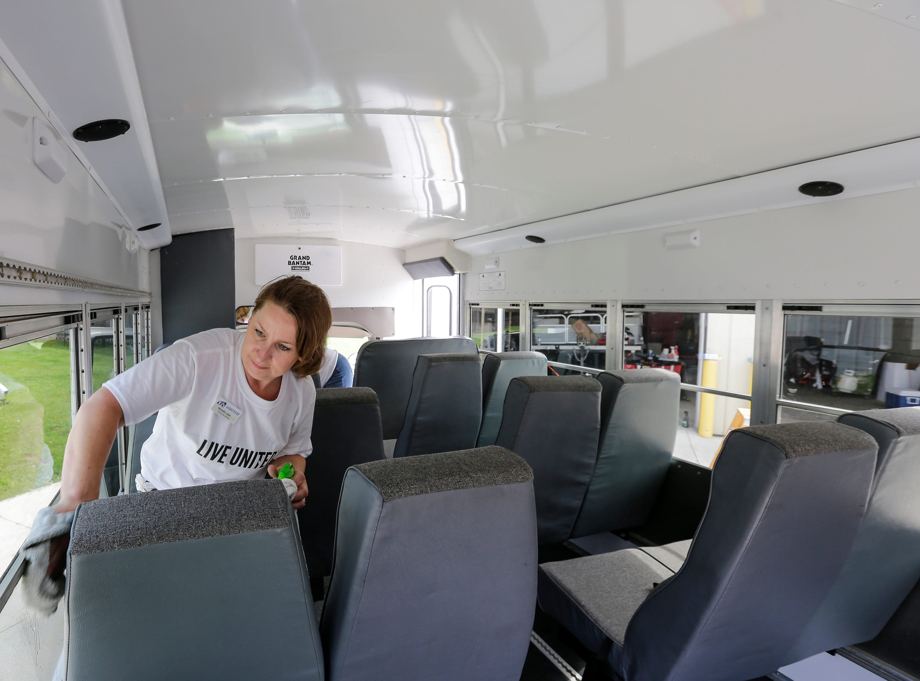 Michelle Leider of Lakeshore Technical College cleans windows on the Salvation Army bus during the United Way's Day of Action at the Salvation Army Thursday, June 21, 2018, in Manitowoc, Wis. Volunteers spread out across the community to help non-profits and those in need as part of United Way's Day of Action. Josh Clark/USA TODAY NETWORK-Wisconsin