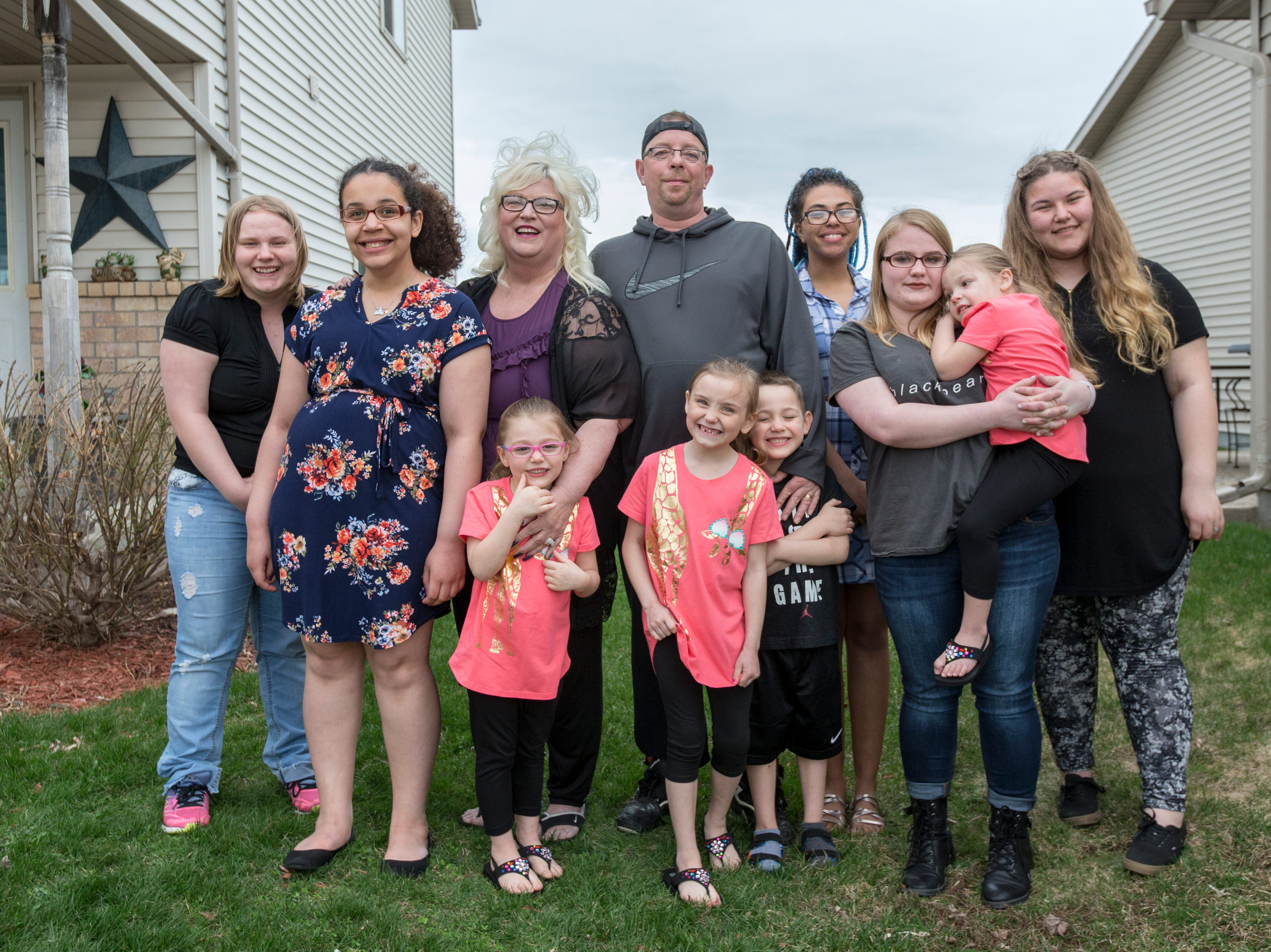 Becky and Rob Brooks, center, pose for a portrait with their family in front of their home Thursday, May 3, 2018, in Manitowoc, Wis. From left, Danyell, 17; Isabella, 16; Anna, 4; October, 6; Brian, 6; Cristel, 20; Skylar, 17; Charlie, 3; and their granddaughter Bianca Michel, 13. All are legally adopted except for October who has been reunited with her mother but is still thought of as family. The Brooks have taken in 14 foster children over the years and adopted nine of them.