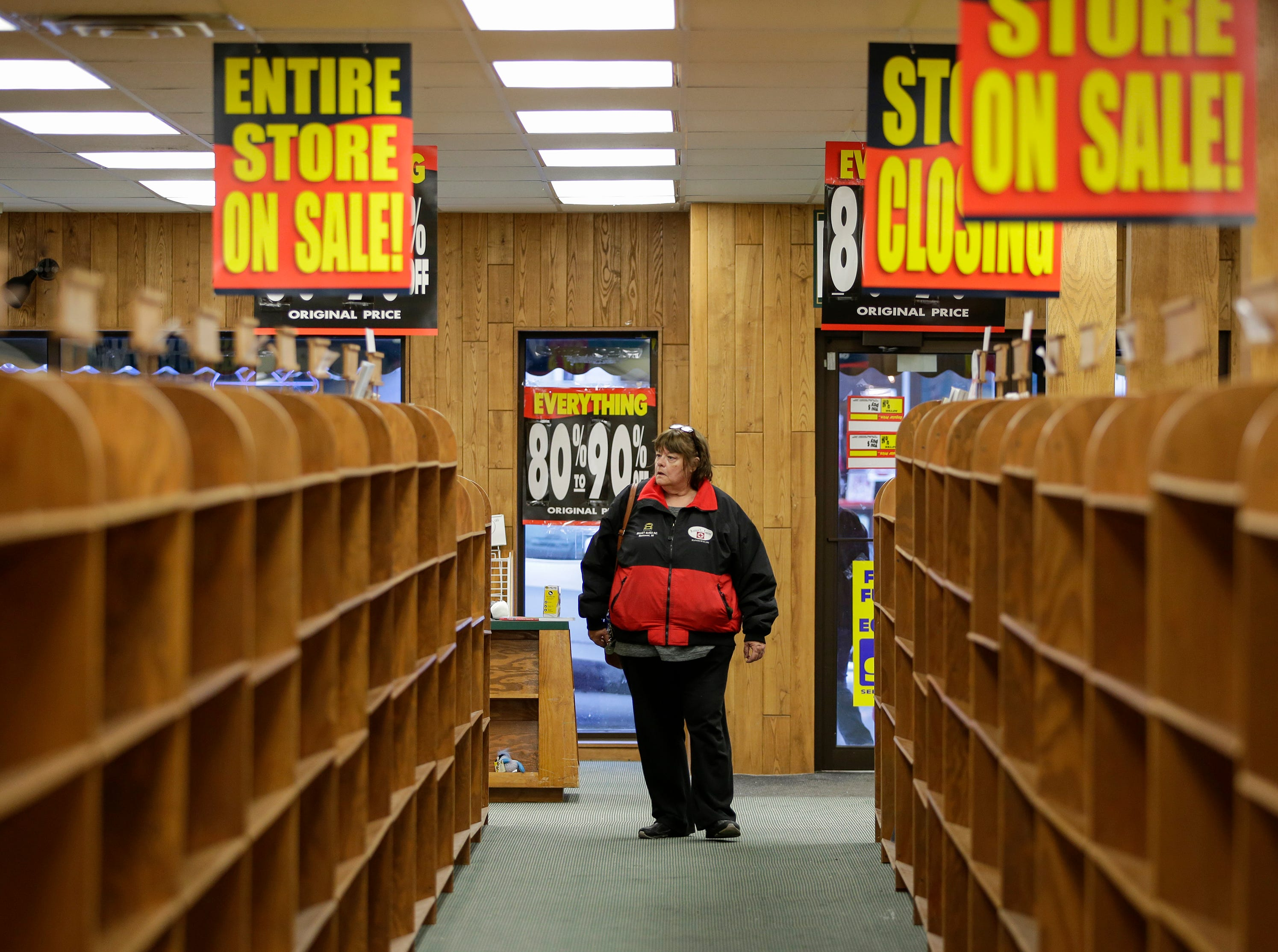 Lori Maltby walks through empty book shelves at Book World before it closes for good Thursday, Jan. 18, 2018, in Manitowoc, Wis. The downtown bookstore closed Saturday, Jan. 20th, 2018, after the company announced it would be closing all its 45 stores including 20 in Wisconsin. Josh Clark/USA TODAY NETWORK-Wisconsin