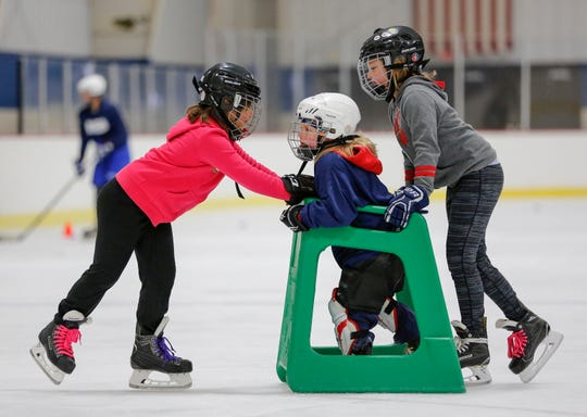 Lizzie Wallander, 9, left, and Amelia Suchomel, 9, teach Zoe Schloseky, 4, how to skate during the Manitowoc County Youth Hockey Association's Girls Try Hockey event at the County Ice Center Saturday, October 13, 2018, in Manitowoc, Wis. Suchomel and Wallander both play on the Pee Wee team and were on the ice teaching other girls about the sport. Joshua Clark/USA TODAY NETWORK-Wisconsin