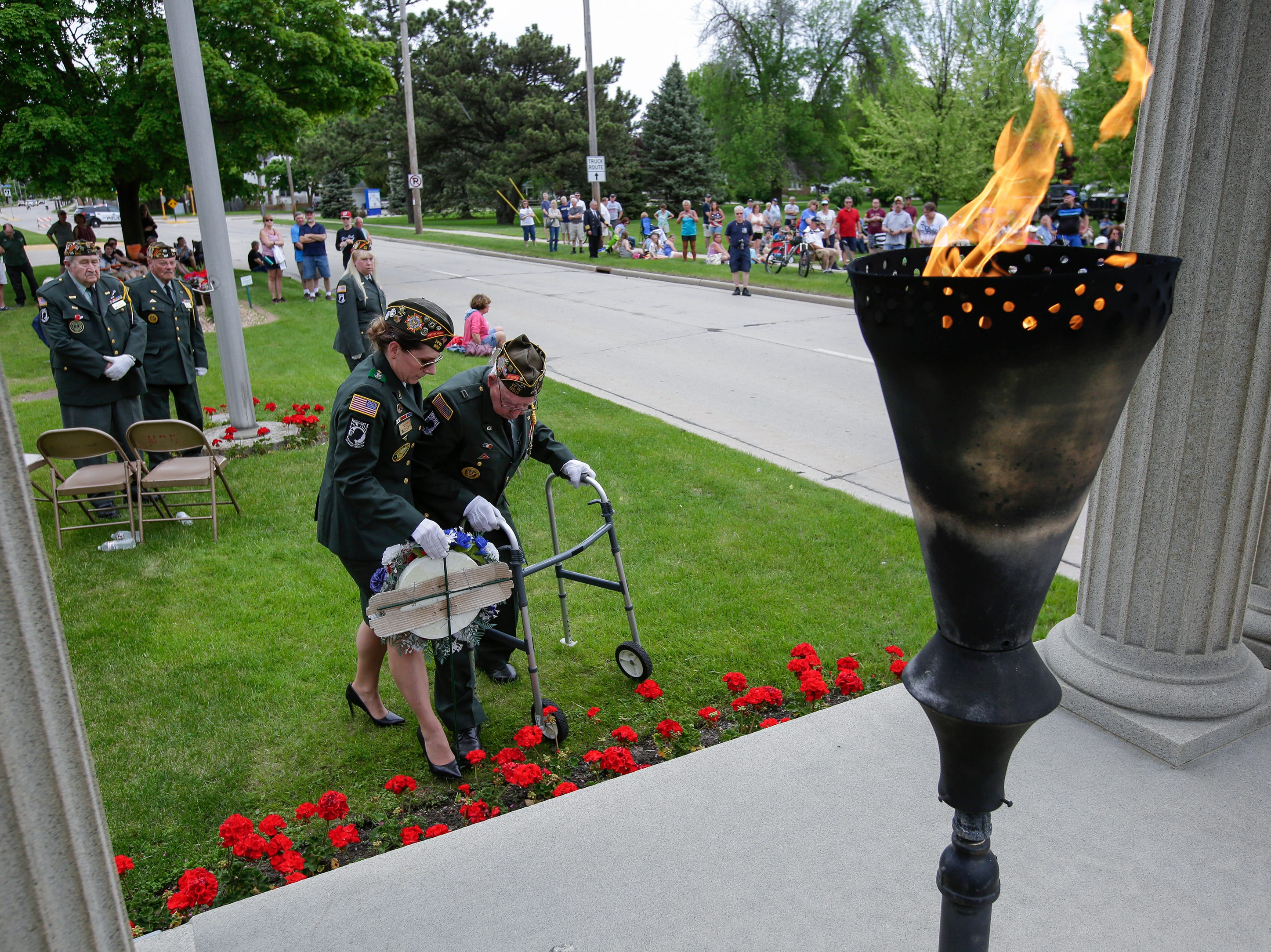 VFW honor guard Julie Rozum, left, and color guard captain Harold Kummer place a commemorative wreath in front of the Soldiers and Sailors Monument as the Eternal Flame burns in remembrance of those who served during the Memorial Day ceremony Monday, May 28, 2018, in Manitowoc, Wis. Josh Clark/USA TODAY NETWORK-Wisconsin