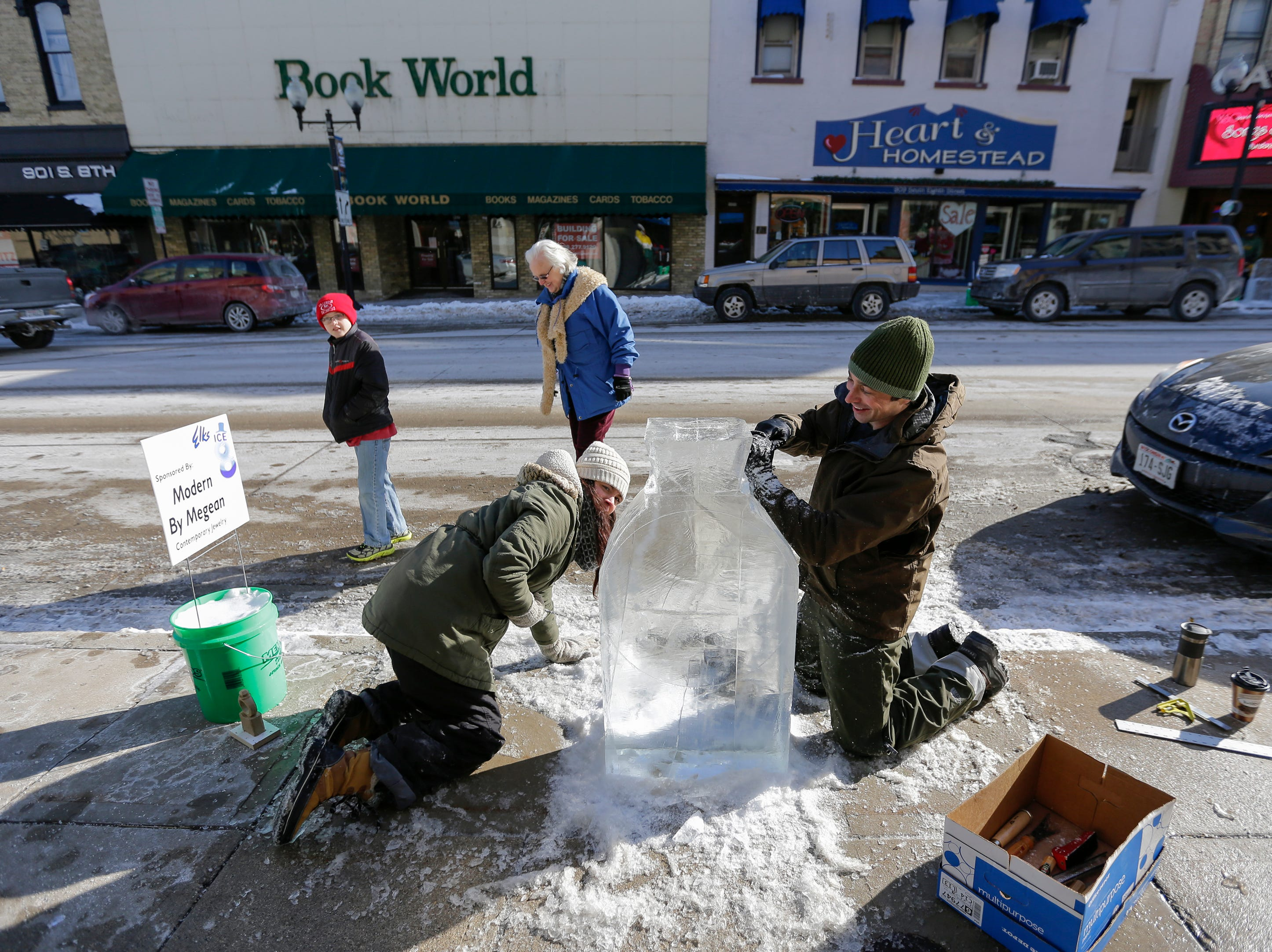 Samantha Deeley, front left, and Patrick Burke work on an ice carving of a diamond ring outside Modern by Megean as people walk down 8th Street watching sculptors work during the Ice on 8th winter festival Saturday, Feb. 10, 2018, in Manitowoc, Wis. Josh Clark/USA TODAY NETWORK-Wisconsin