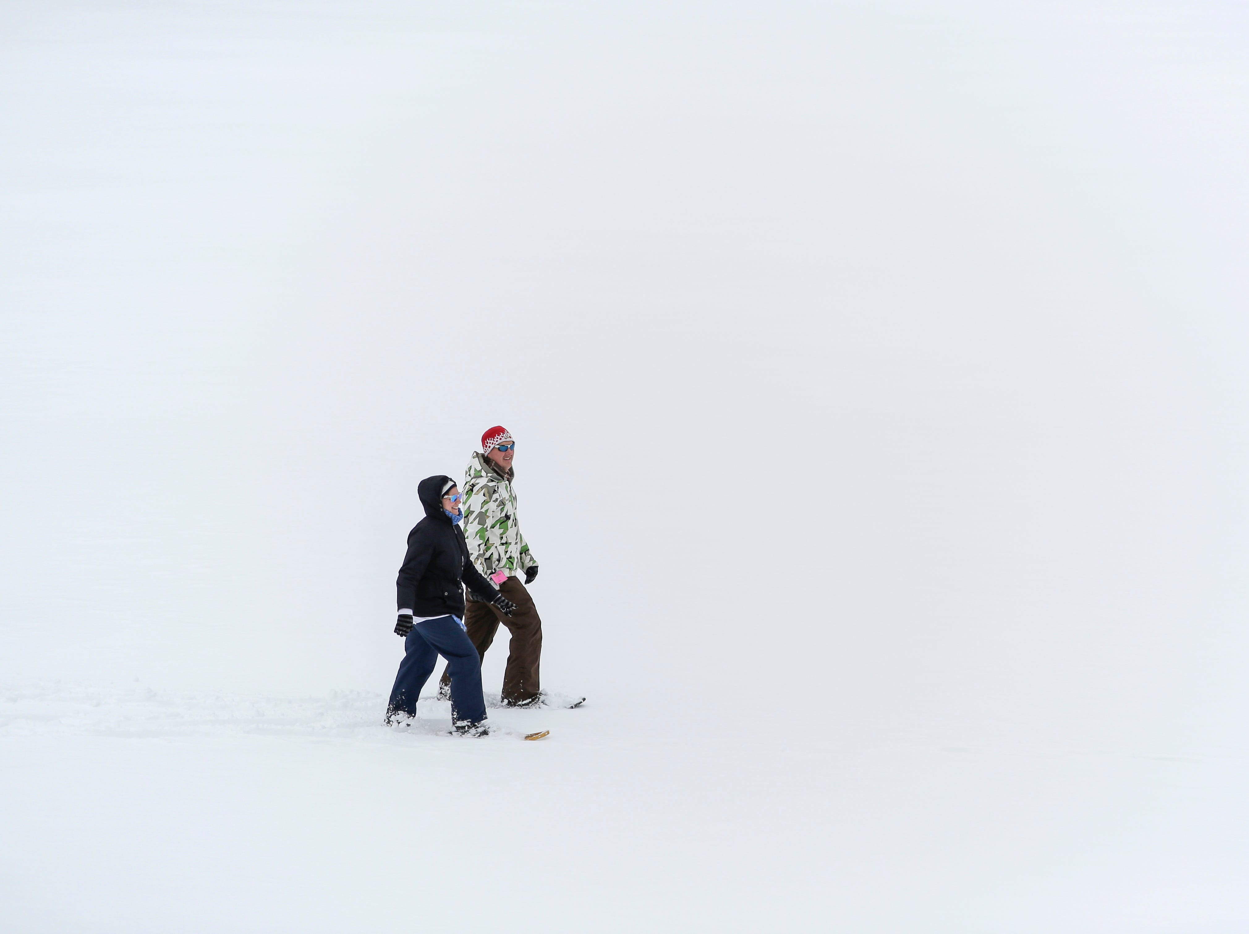 A woman and a man snow shoe through Silver Creek Park after winter storm Evelyn dropped more than a foot of snow on the area Monday, Apr. 16, 2018, in Manitowoc, Wis. Josh Clark/USA TODAY NETWORK-Wisconsin