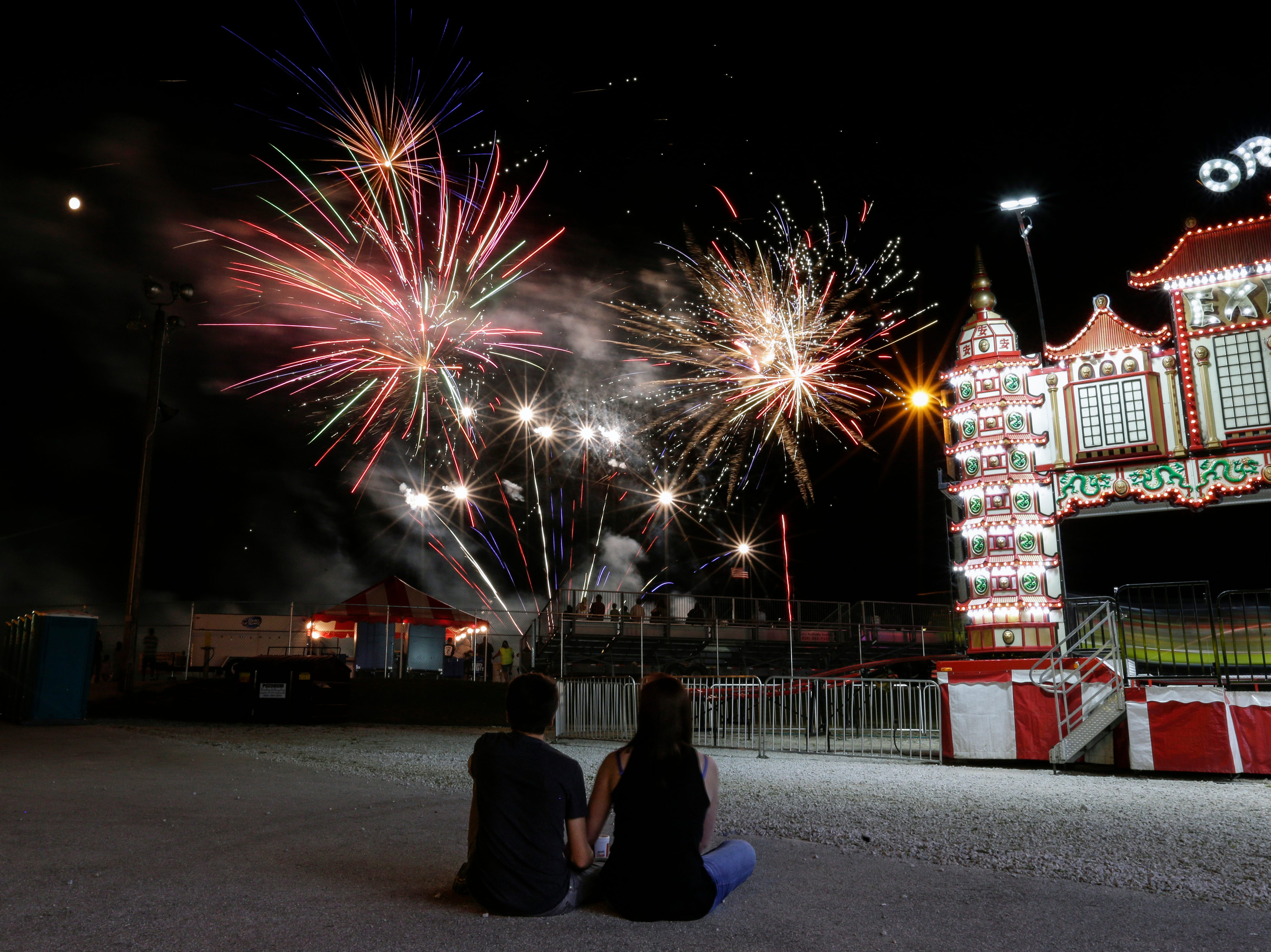 Max Schoett, 16, and Olivia Lutterman, 17, of Manitowoc watch the fireworks go off next to a nearly full moon at the Manitowoc County Fair Wednesday, August 22, 2018, in Manitowoc, Wis. The show capped off the fair's first full day of activities at the fairgrounds. Josh Clark/USA TODAY NETWORK-Wisconsin